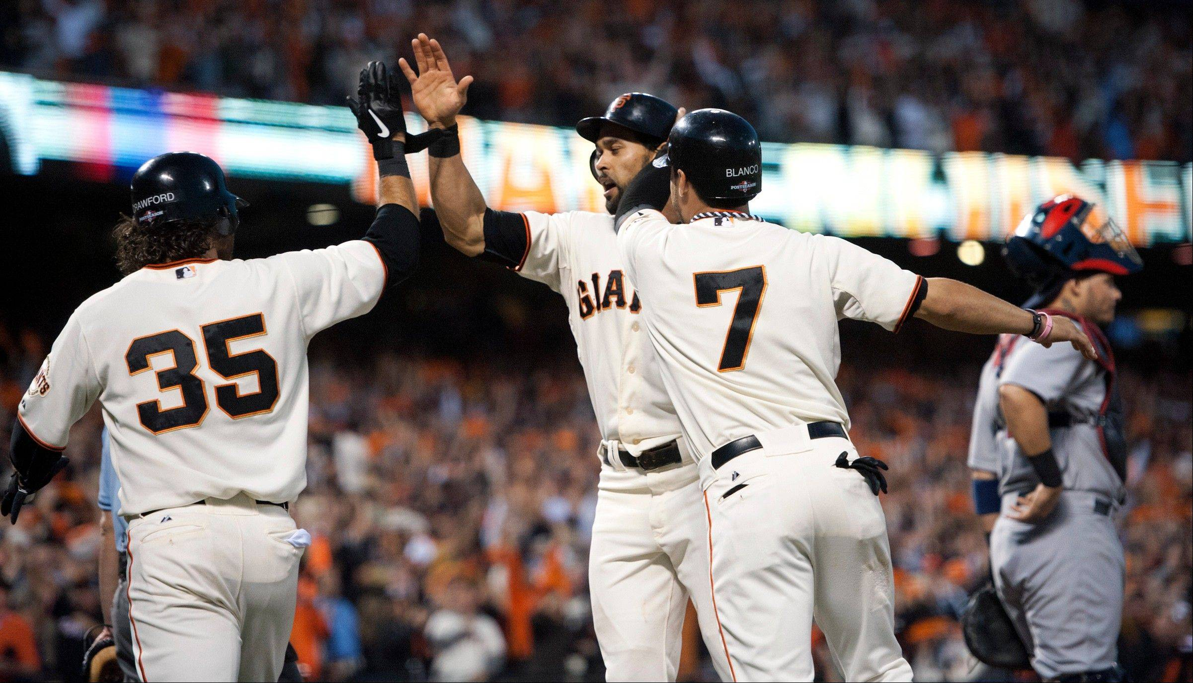 The San Francisco Giants' Brandon Crawford (35), Gregor Blanco (7) and Angel Pagan celebrate at the plate Monday after scoring on a fielding error by St. Louis Cardinals left fielder Matt Holliday on a single by Giants' Marco Scutaro during the fourth inning of Game 2 of the National League championship series in San Francisco.