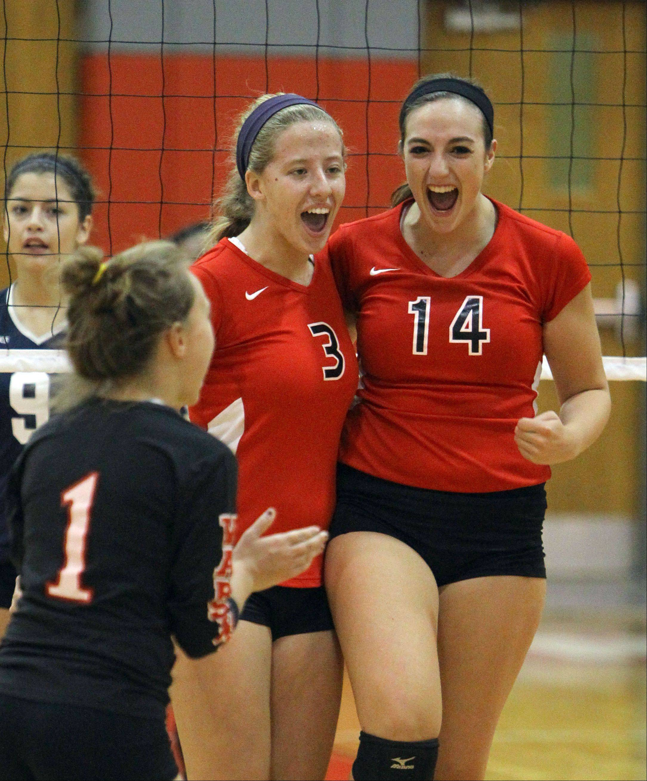 From left, Mundelein's Elizabeth Cameron, Courtney Perreault and Ashley Dolin celebrate after winning a point against Round Lake at Mundelein on Monday.