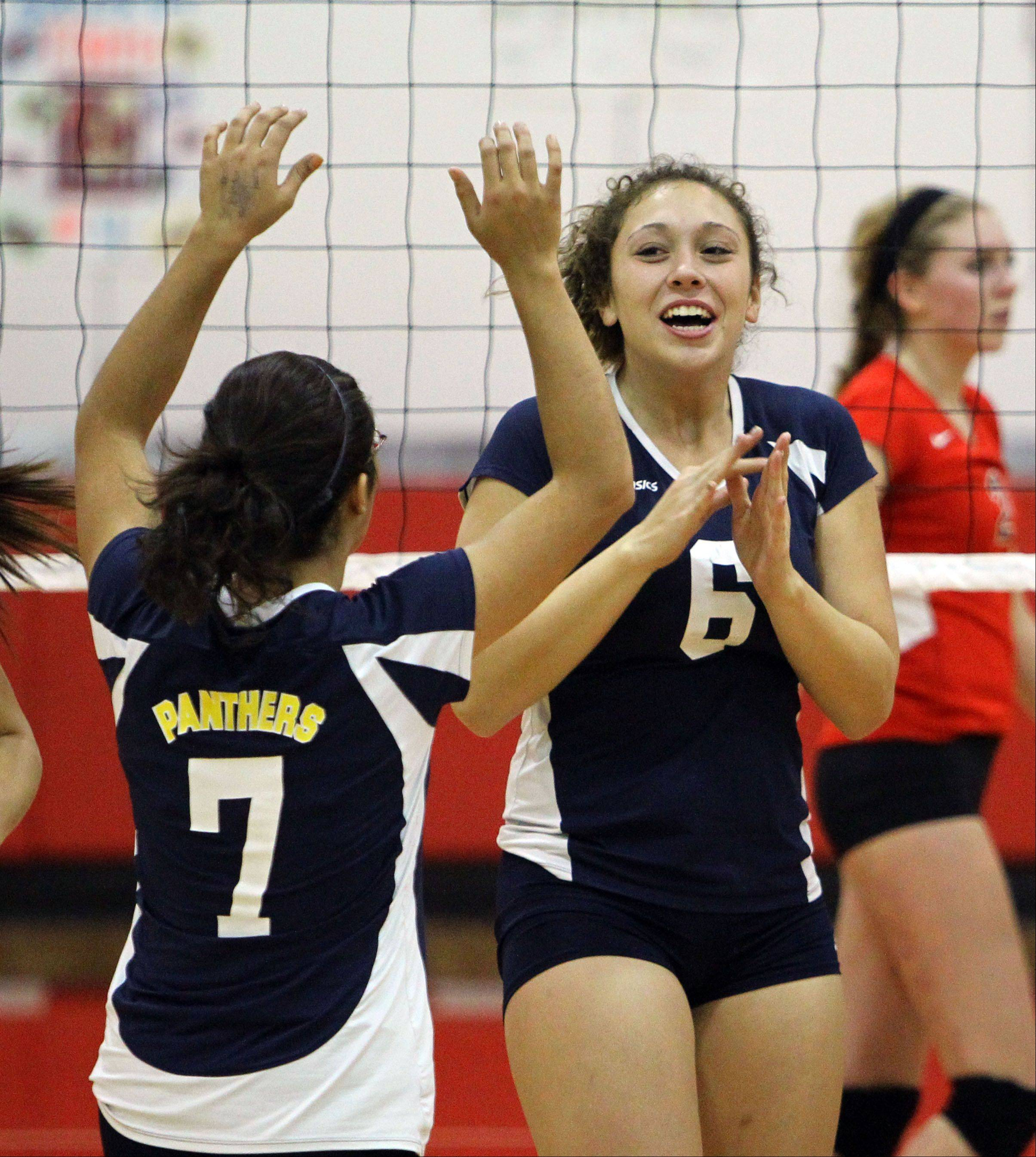 Round Lake's Izzy Rodriguez, left, and Dominique Gonzales celebrate after winning a point Monday night at Mundelein.