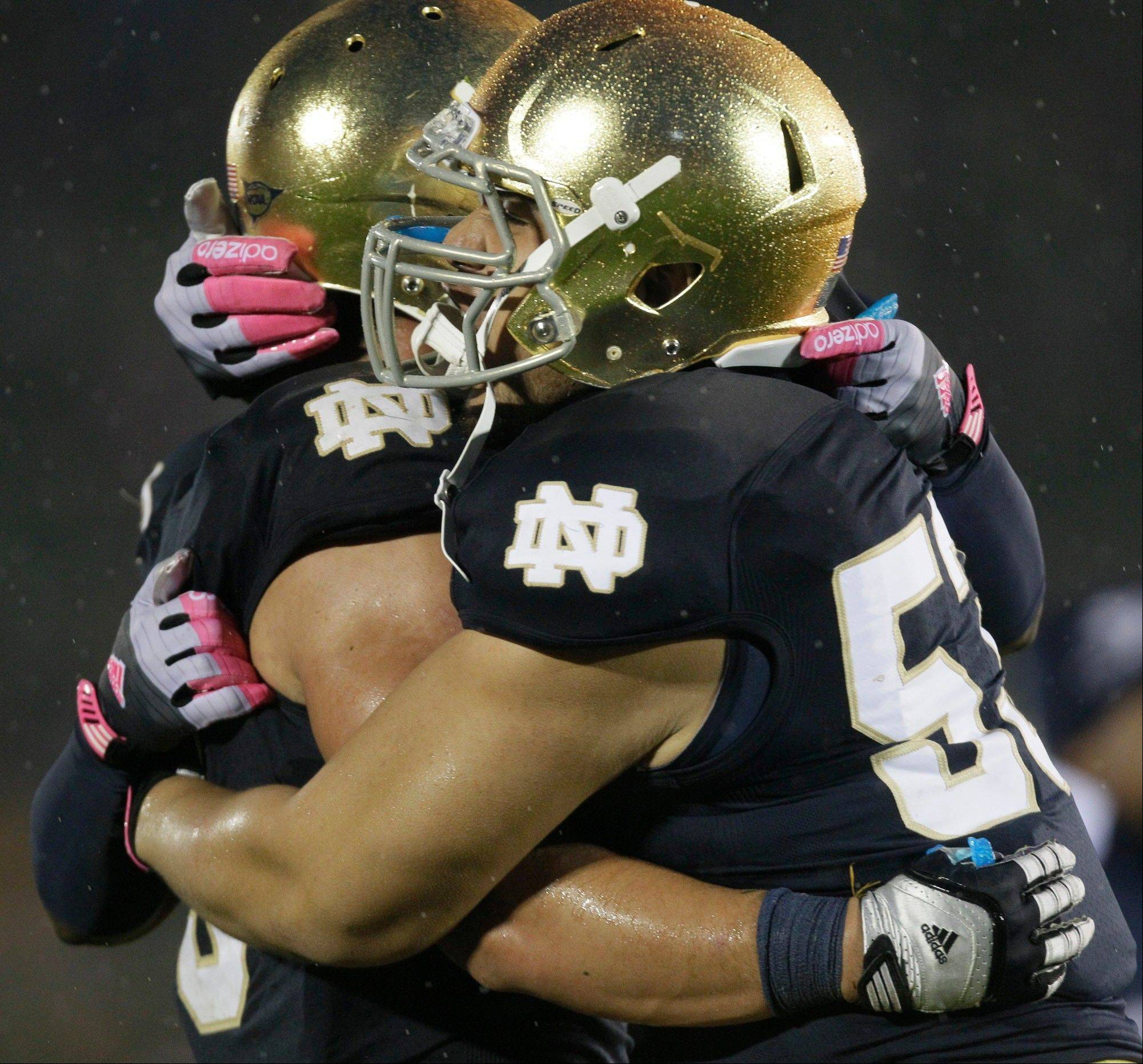 Notre Dame linebacker Manti Te'o, left, celebrates with defensive end Justin Utupo (53) after Notre Dame defeated Stanford 20-13 in overtime Saturday in South Bend, Ind.