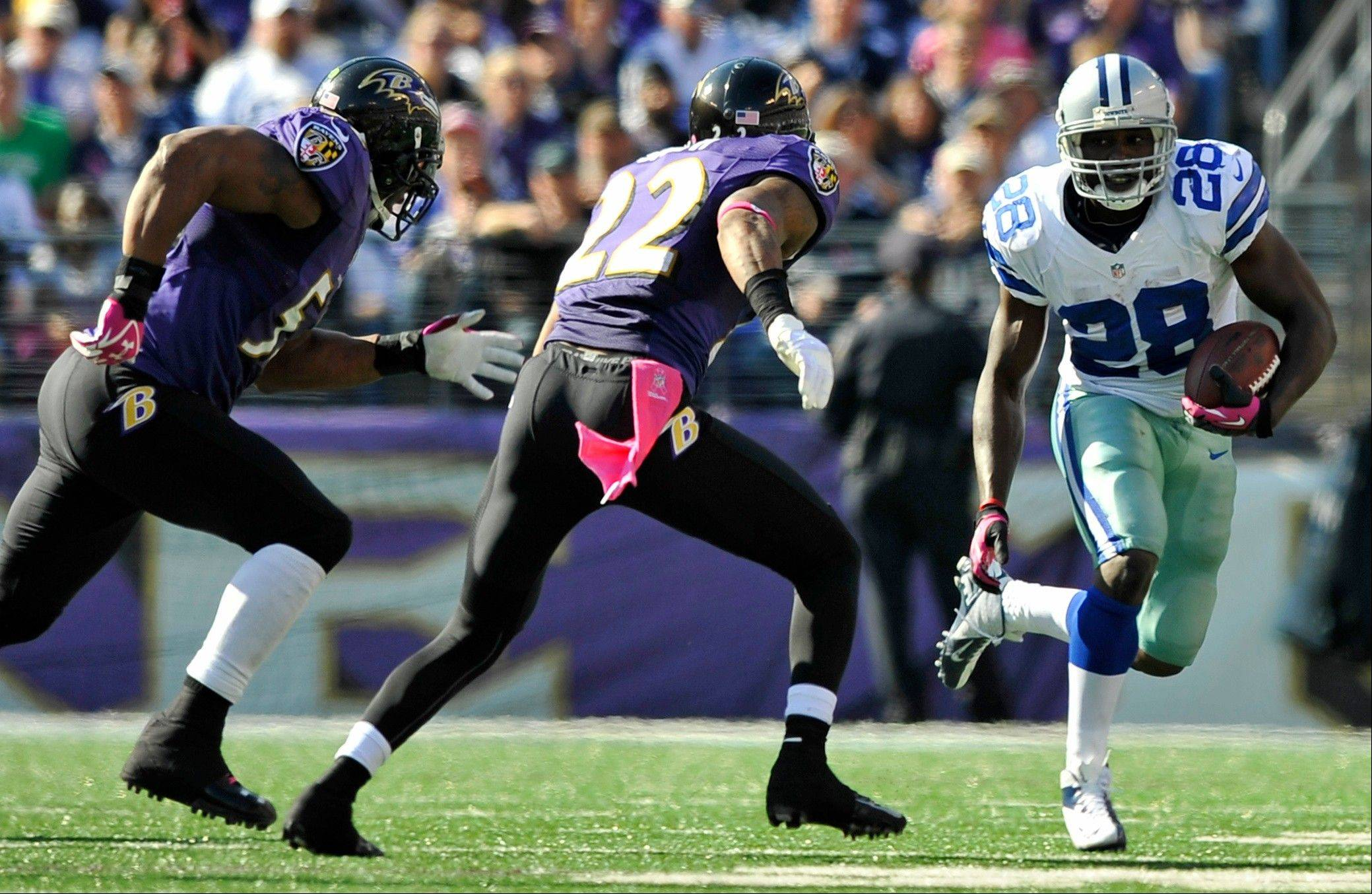 Dallas Cowboys running back Felix Jones, right, rushes past Baltimore Ravens defenders Ray Lewis, left, and Jimmy Smith Sunday during the second half in Baltimore.
