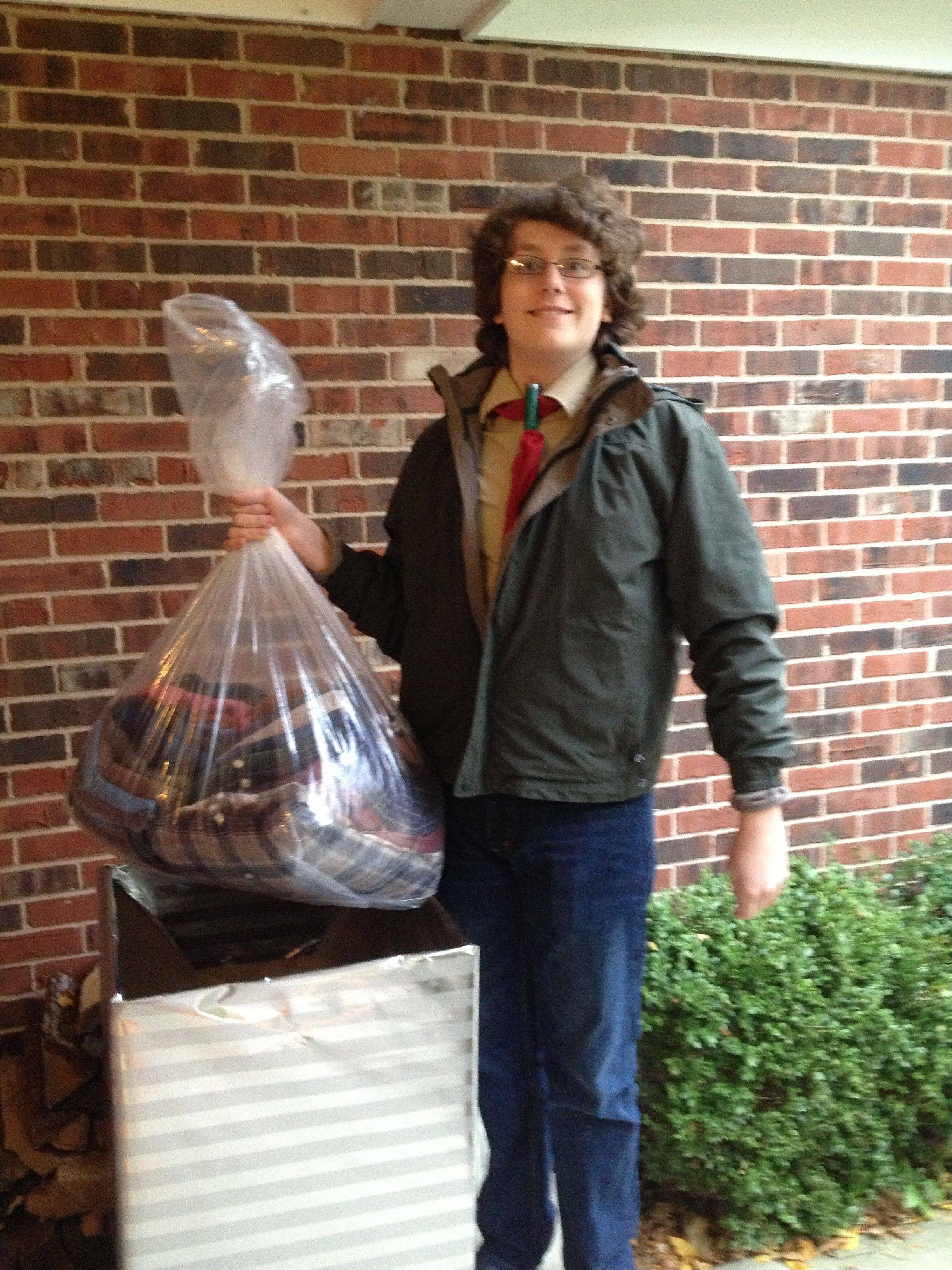 Life Scout Cole Johnston picks up donations from one of the boxes he set up to collect items for the Society of the Preservation of Human Dignity's resale shop. Johnston organized the donation drive for his Eagle Scout project.