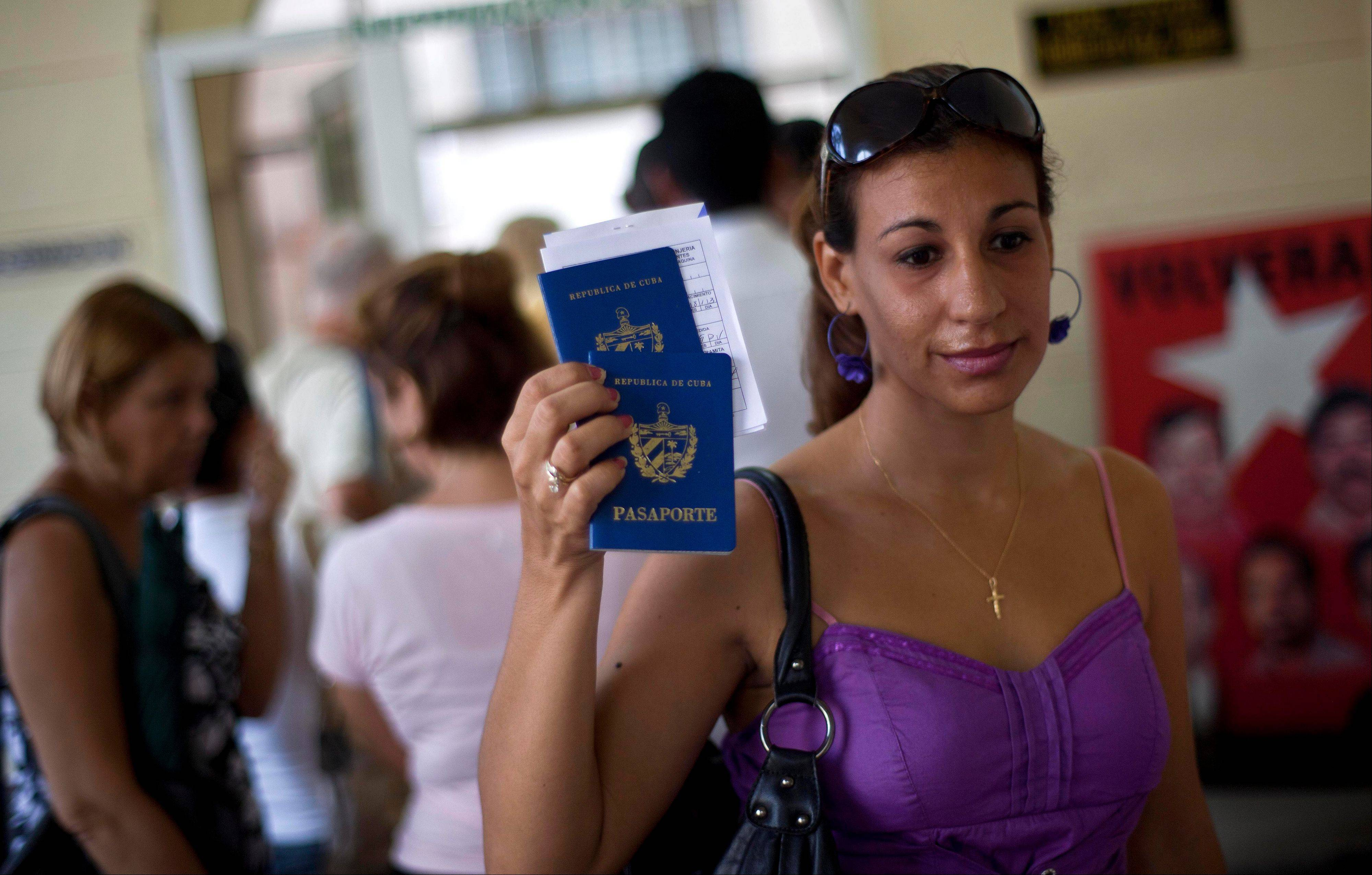 A woman shows her passport and that of her son to reporters as she leaves an immigration office in Havana on Tuesday. The Cuban government announced Tuesday it will no longer require islanders to apply for an exit visa.