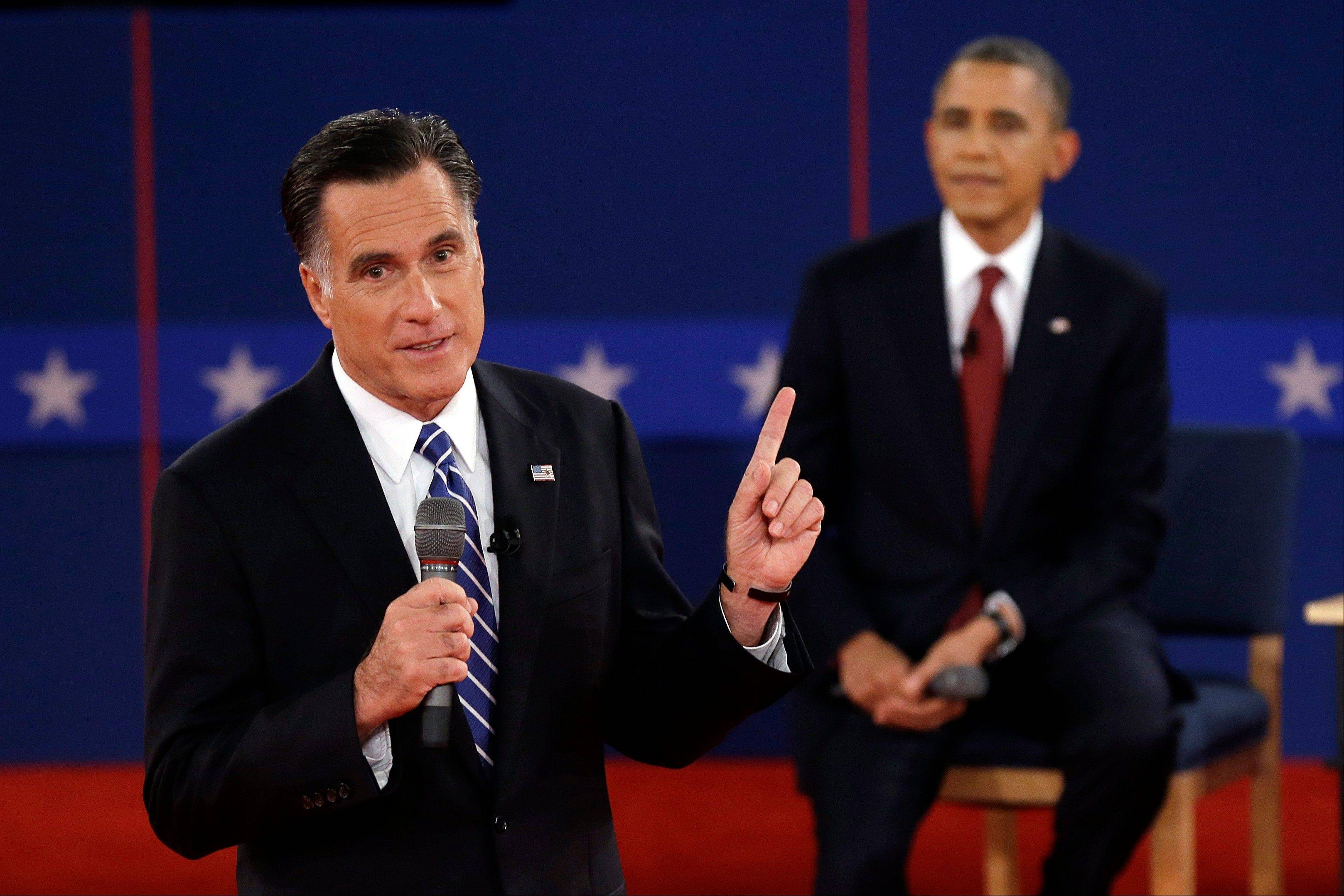 Republican presidential nominee Mitt Romney answers a question as President Barack Obama listens during the second presidential debate at Hofstra University, Tuesday, Oct. 16, 2012, in Hempstead, N.Y.