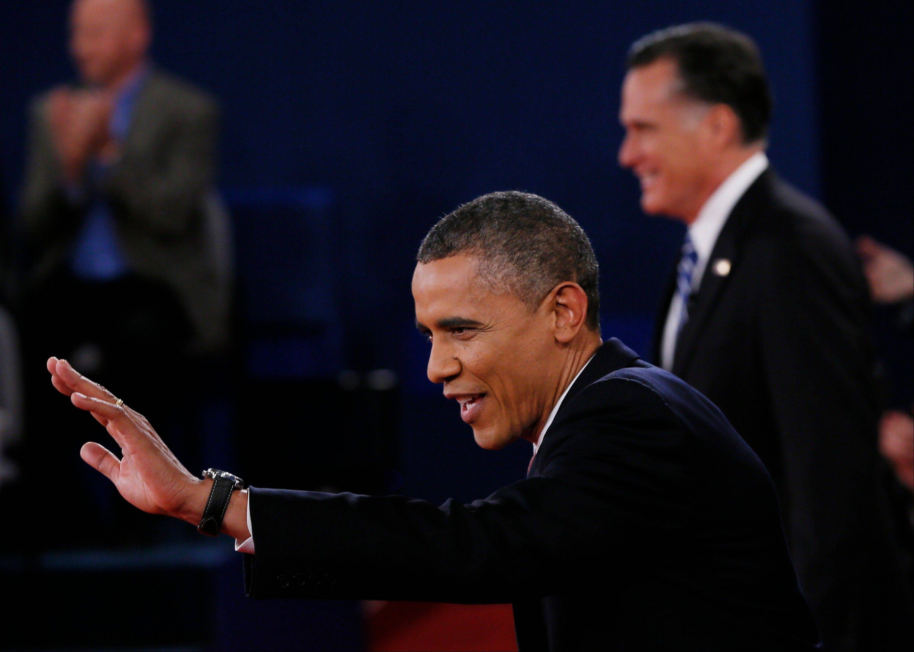 President Barack Obama, left, waves at the start of the second presidential debate with Republican presidential nominee Mitt Romney at Hofstra University, Tuesday, Oct. 16, 2012, in Hempstead, N.Y.
