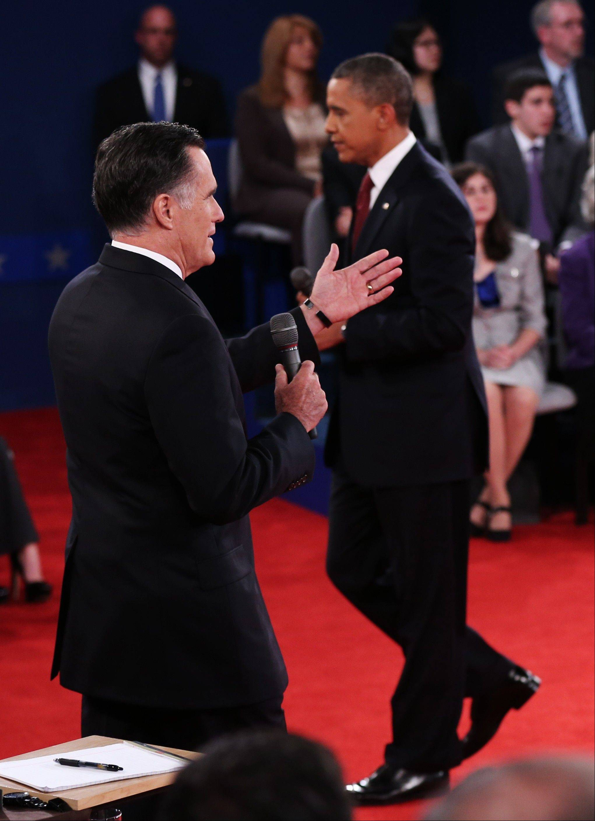 President Barack Obama, right, walks past as Republican presidential nominee Mitt Romney members of the audience during the second presidential debate at Hofstra University, Tuesday, Oct. 16, 2012, in Hempstead, N.Y.