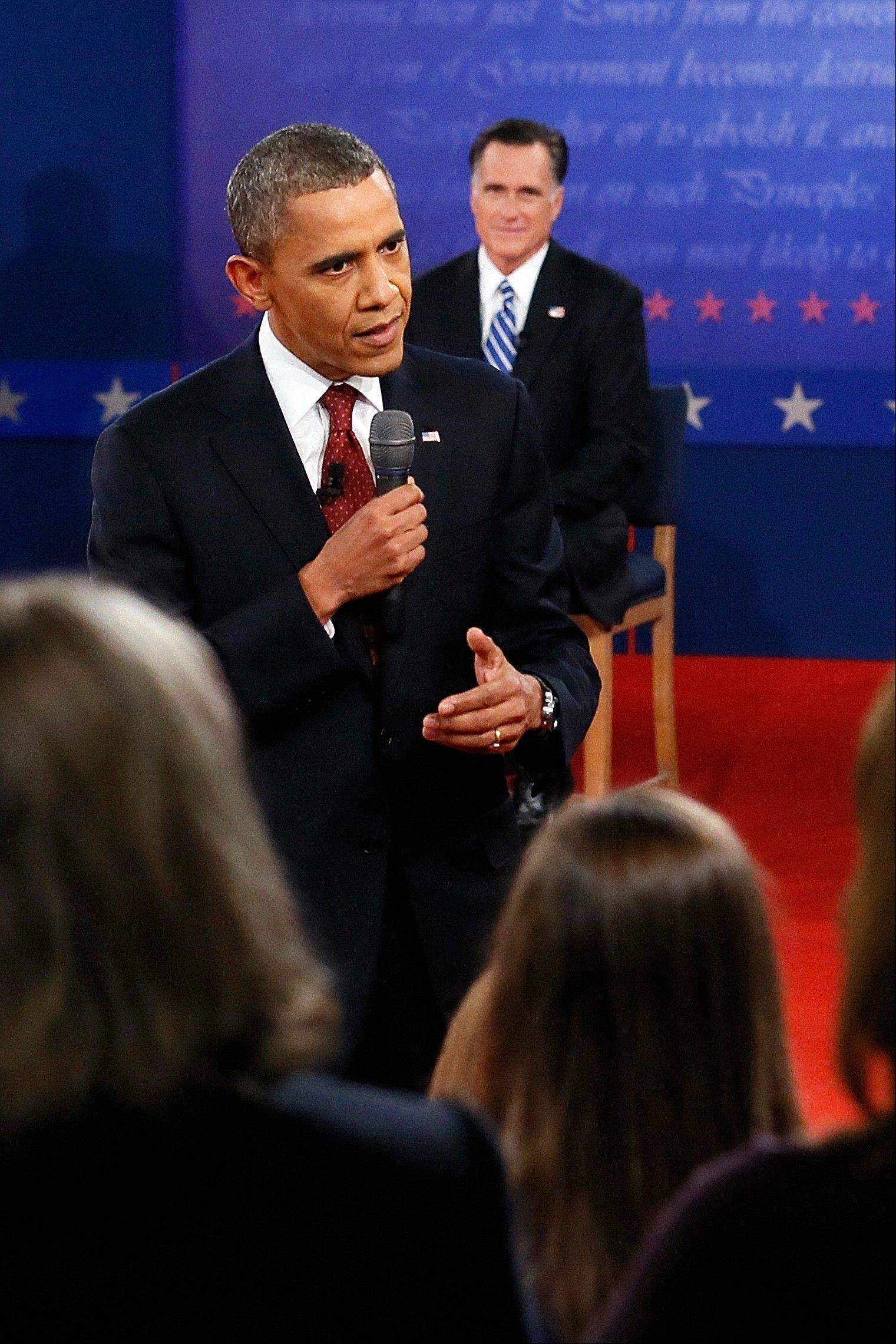 President Barack Obama answers a question as Republican presidential nominee Mitt Romney listens during the second presidential debate at Hofstra University, Tuesday, Oct. 16, 2012, in Hempstead, N.Y.