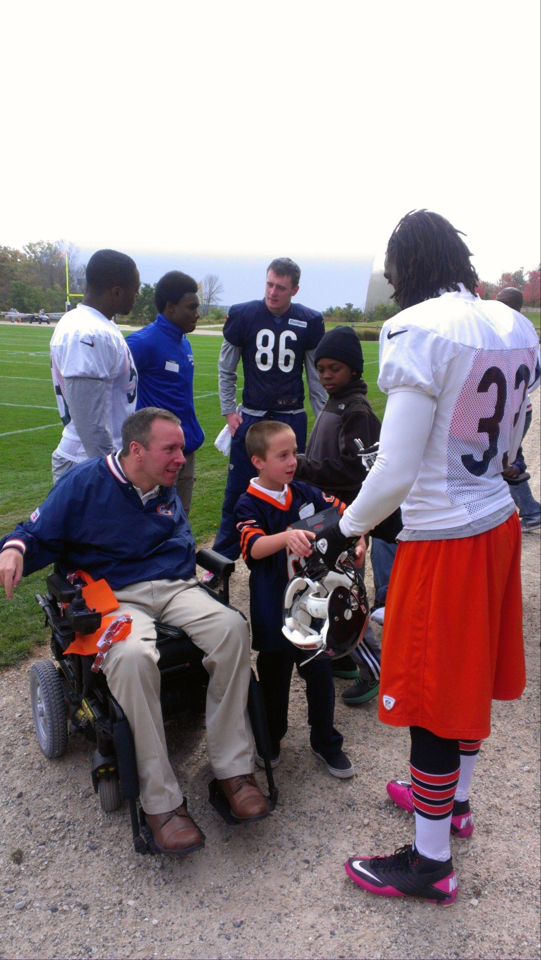 Bears All-Pro cornerback Charles Tillman visits with Steve Herbst and his son, Jack, of Palatine. Injured in a football practice 32 years ago, Herbst is on the board of the Gridiron Alliance charity, which advocates for athletes with catastrophic injuries.