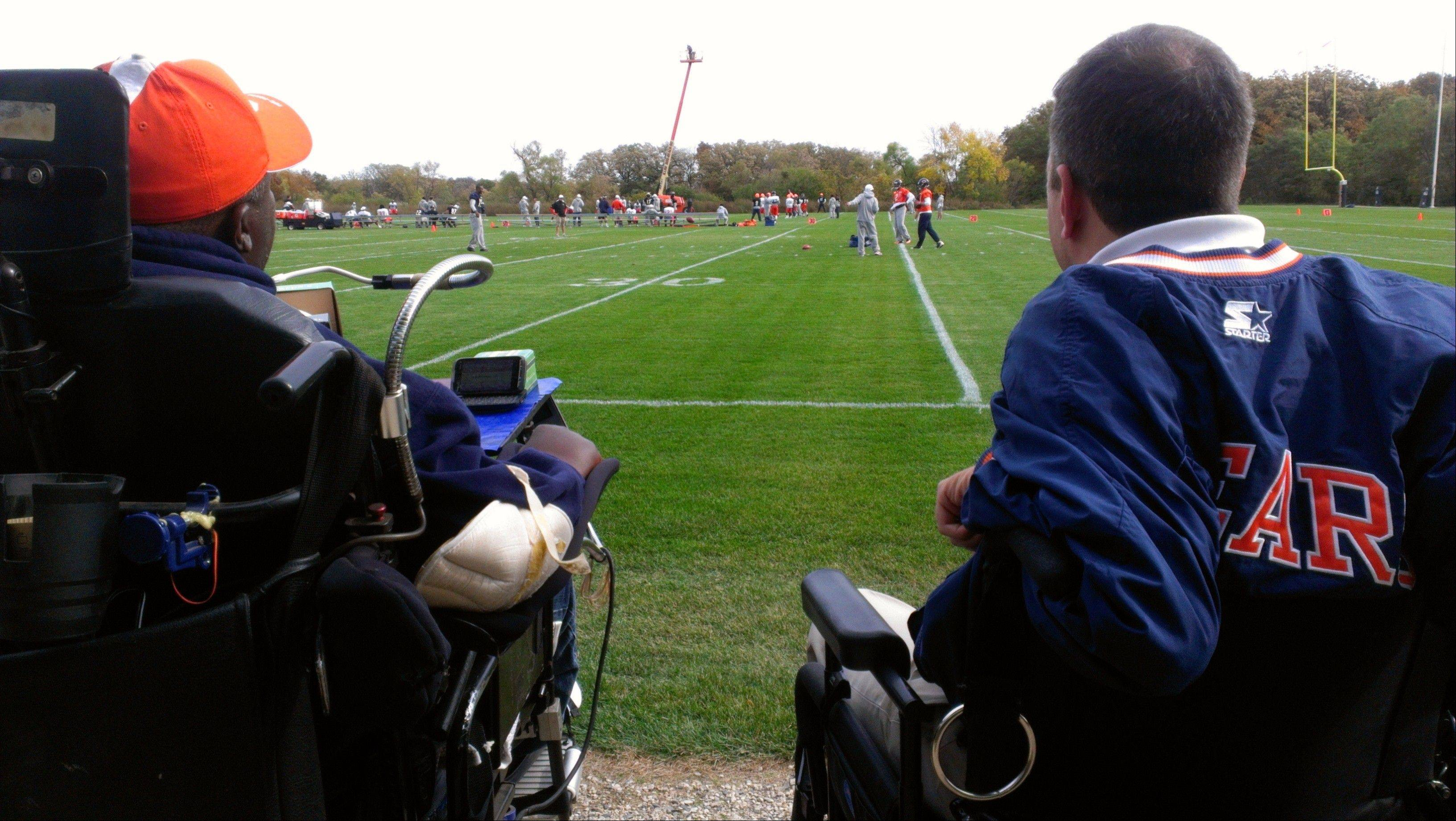 Newly named Gridiron Alliance chairman Kenneth Jennings, left, watches a recent Bears practice with fellow board member Steve Herbst of Palatine. The Gridiron Alliance charity advocates for athletes with catastrophic injuries.