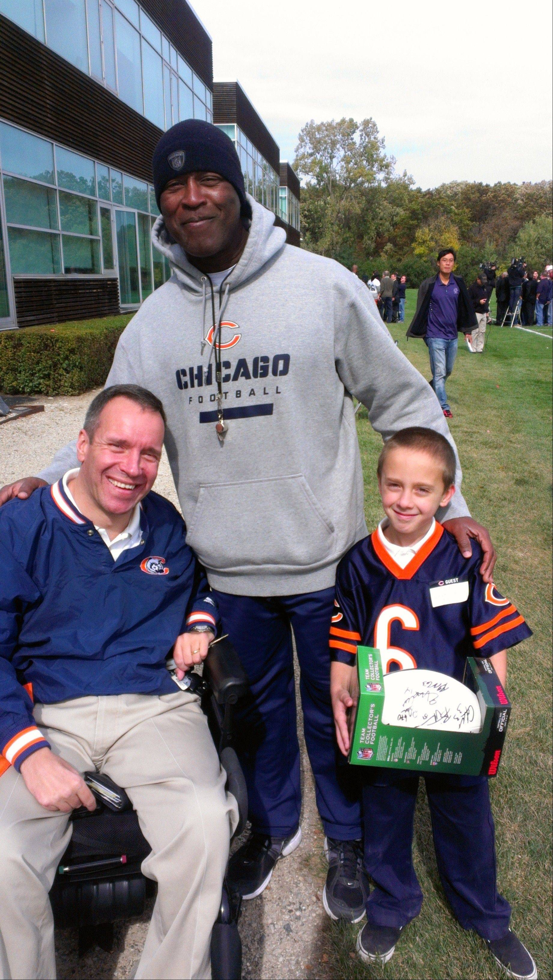 Chicago Bears Coach Lovie Smith, center, lends support to Gridiron Alliance board member Steve Herbst and his son, Jack, of Palatine. Injured in a football practice 32 years ago, Herbst is on the board of the charity, which advocates for athletes with catastrophic injuries.