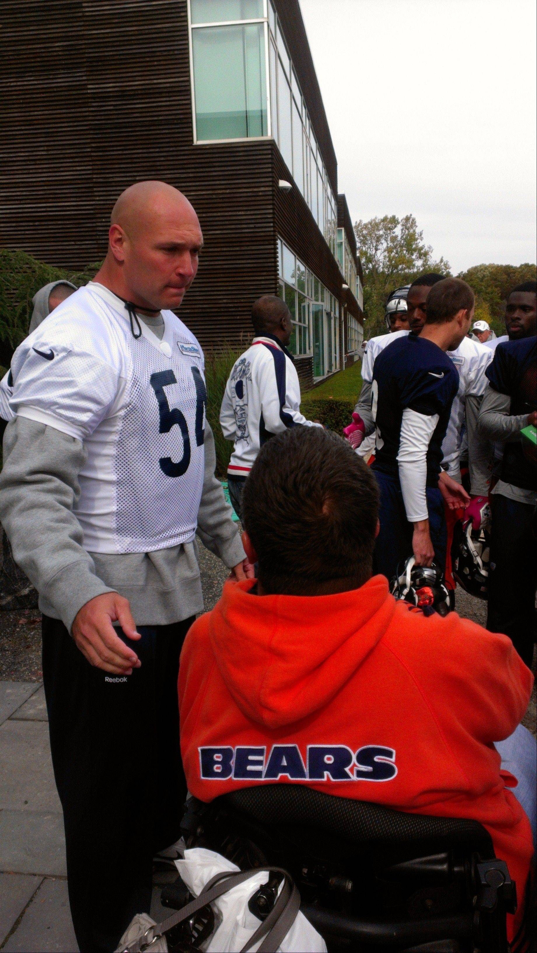 Meeting Bears linebacker Brian Urlacher, left, and seeing his support for athletes with catastrophic injuries spurred Arlington Heights resident Deborah Nelson, executive director of the Gridiron Alliance charity, to buy an Urlacher jersey for her 7-year-old son, Wyatt.
