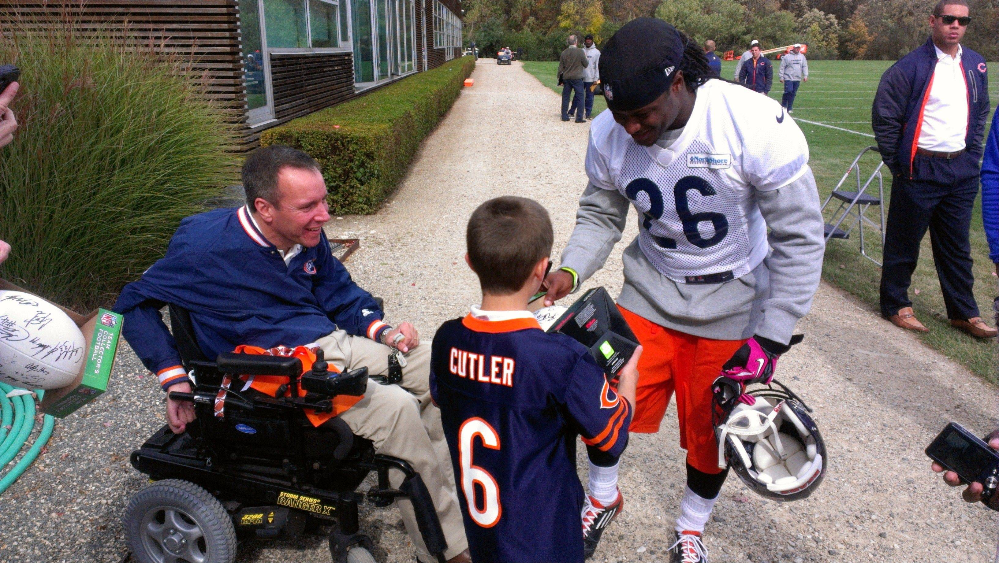 Bears cornerback Tim Jennings visits with Steve Herbst and his son, Jack, of Palatine. Injured in a football practice 32 years ago, Herbst is on the board of the Gridiron Alliance charity, which advocates for athletes with catastrophic injuries.