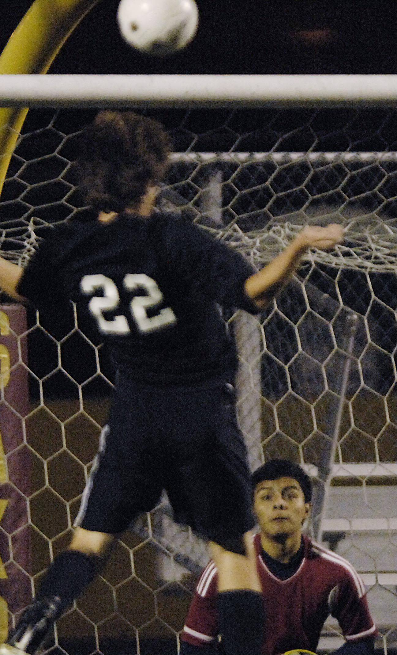 Larkin goalkeeper Aldair Dominguez watches as York's Jack Hayes sends a corner kick over the net with his head Tuesday in the Schaumburg regional playoff game.