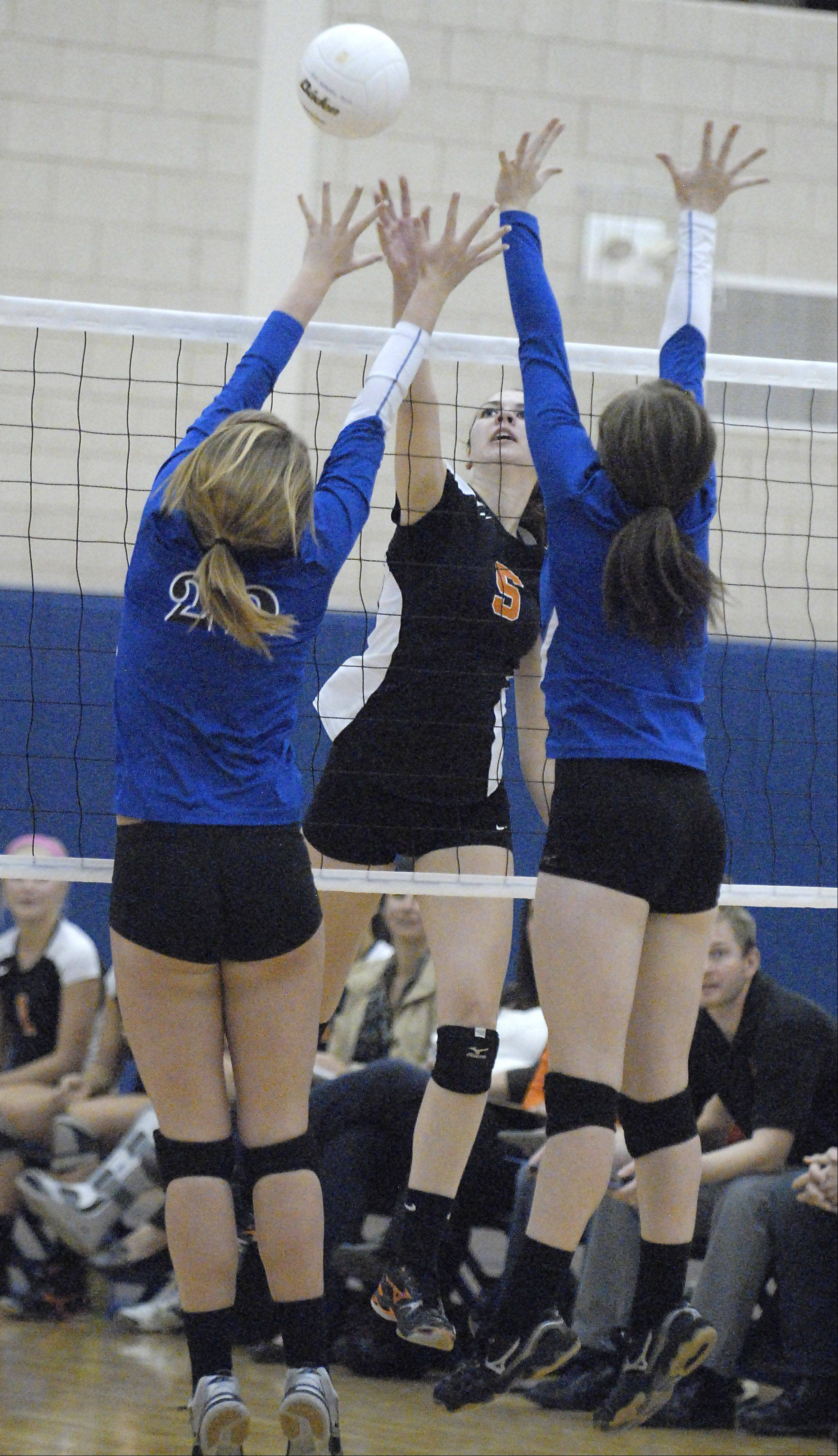 St. Charles East's Nicole Woods spikes past Geneva's Maddie Courter and Renner Burns in game three on Tuesday, October 16.