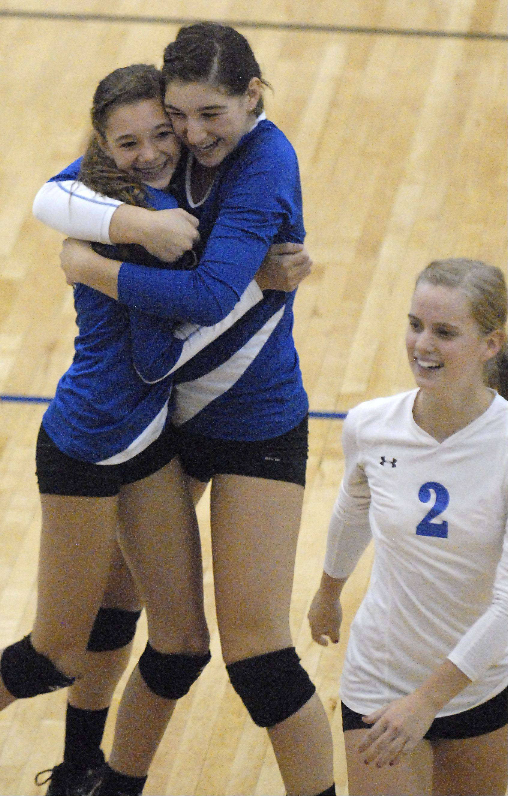 Geneva's Kelsey Wicinski, left, is embraced by older sister, Jess, after scoring a point for the Vikings in the game two battle on Tuesday, October 16.