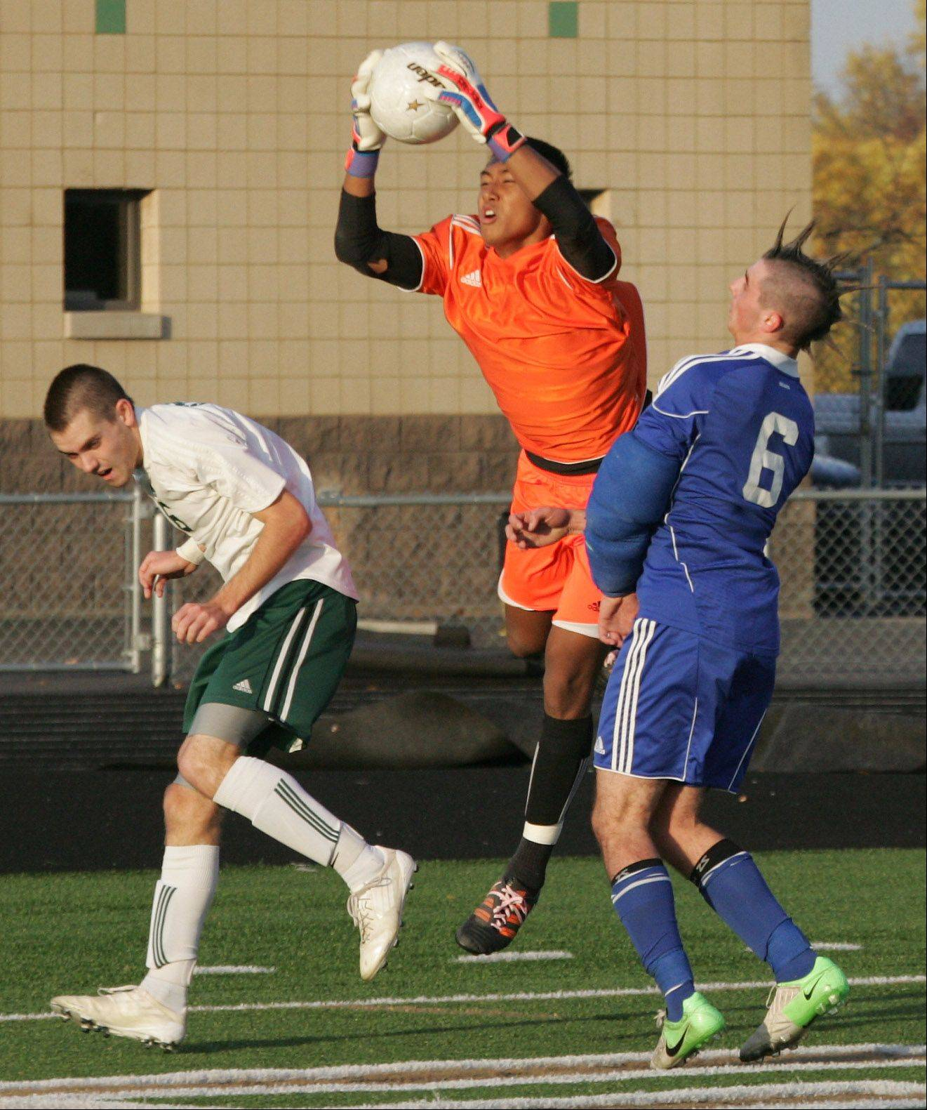 Stevenson goalie Quentin Low grabs the ball between Stevenson defender Alex Smith and Lake Zurich forward John Repplinger during Class 3A regional semifinal play Tuesday in Lincolnshire.