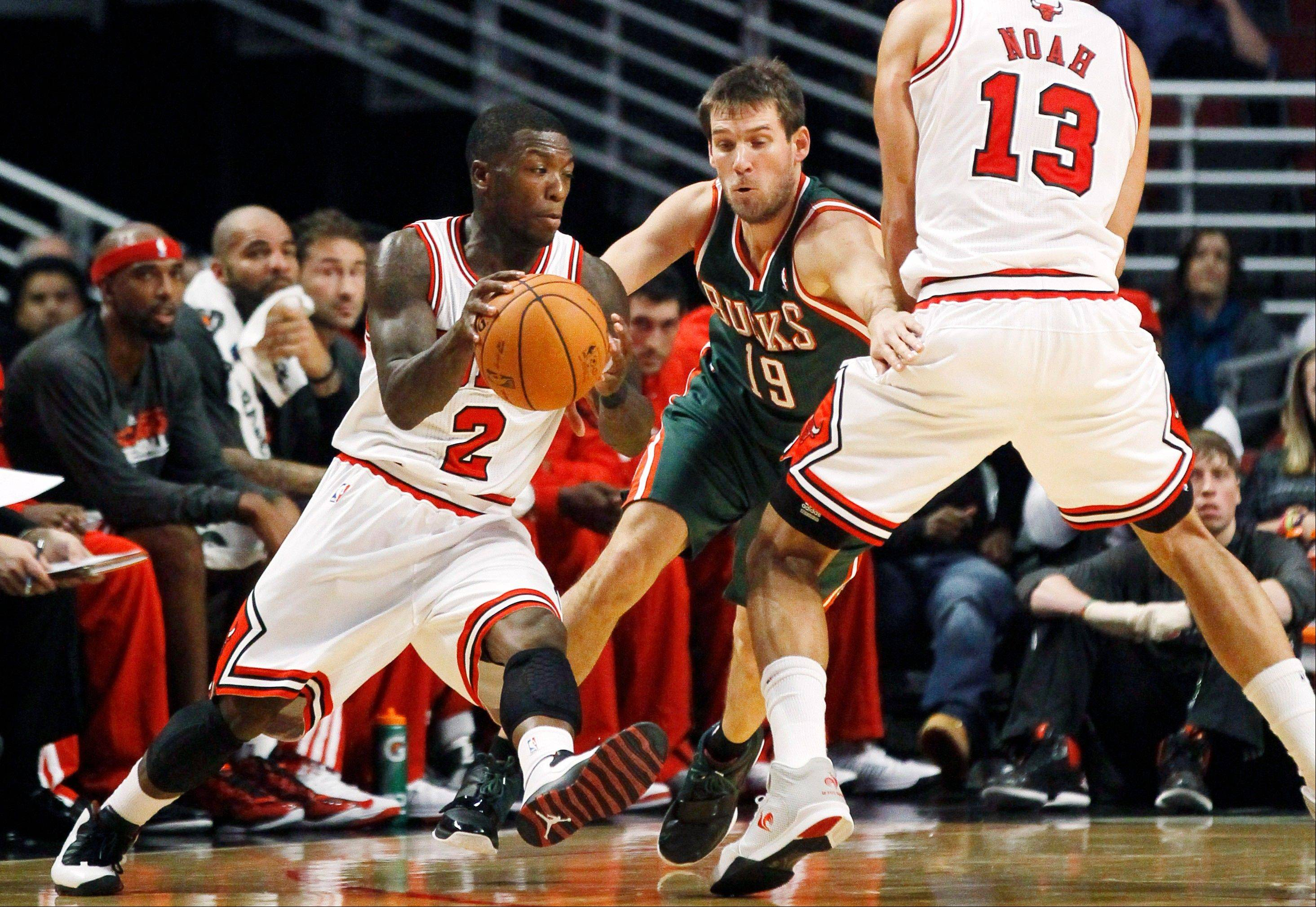 Bulls guard Nate Robinson moves around a screen set by center Joakim Noah as Milwaukee Bucks guard Beno Udrih tries to defend Tuesday during the first half at the United Center.