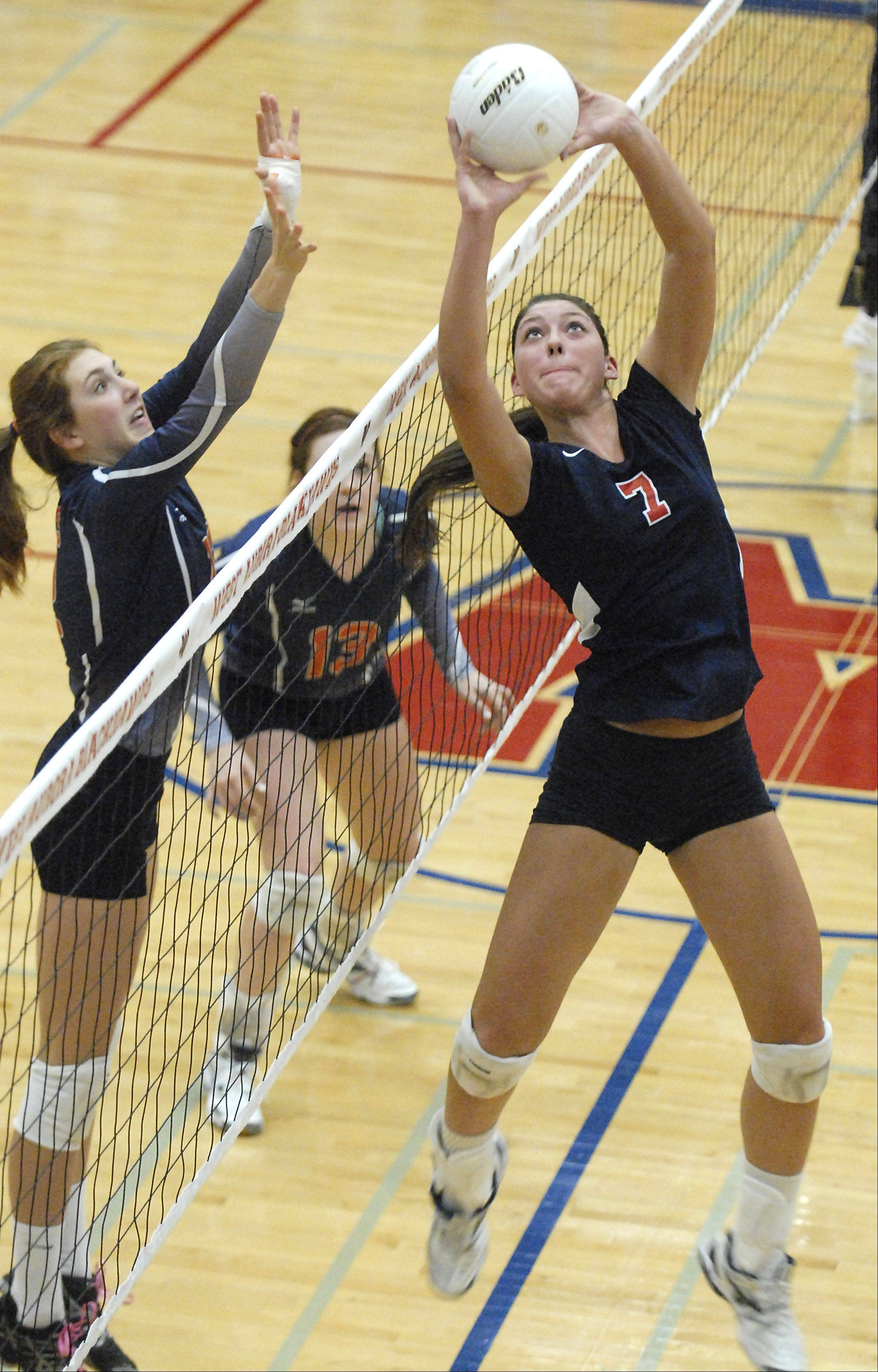 West Aurora's Lauren Carlini tips the ball over the net to Naperville North's Becky Welch and Corinne Gajcak Thursday.