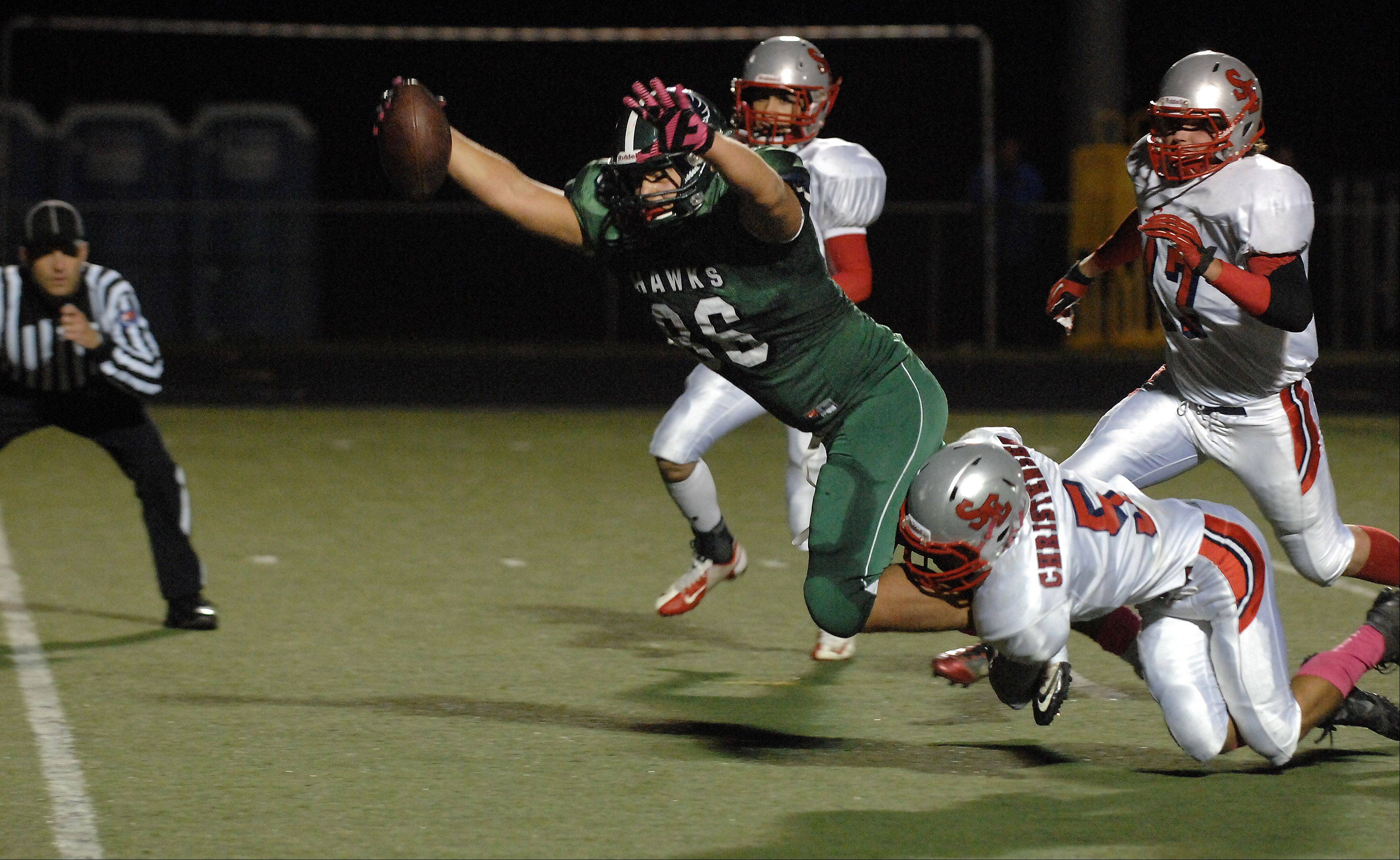 Bartlett's Chris Kantzavelos dives for a touchdown while dragging South Elgin's Tyler Christensen Friday in Streamwood.