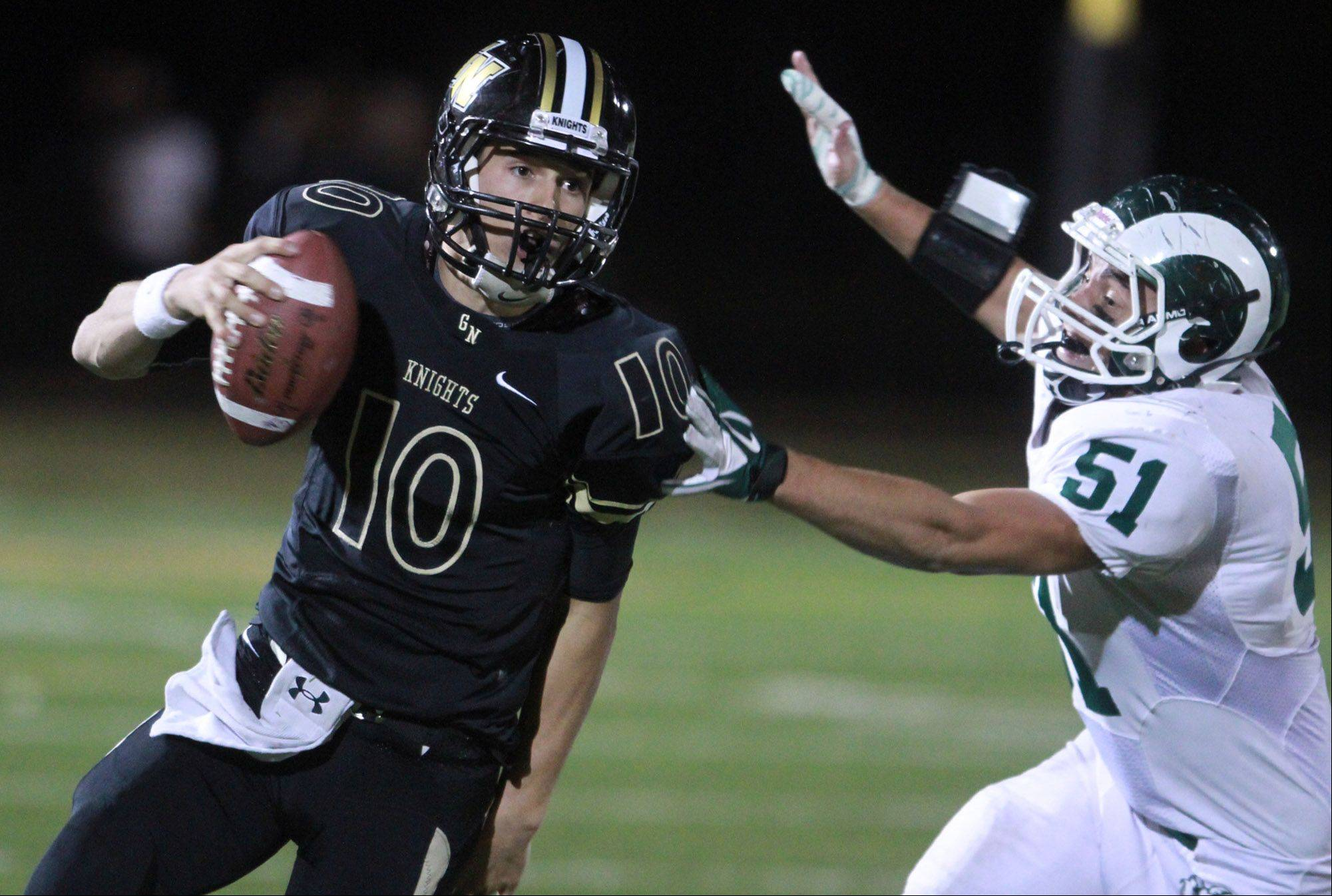 Grayslake North quarterback Anthony Fish slips past Grayslake Central defender Alex McCully Friday.