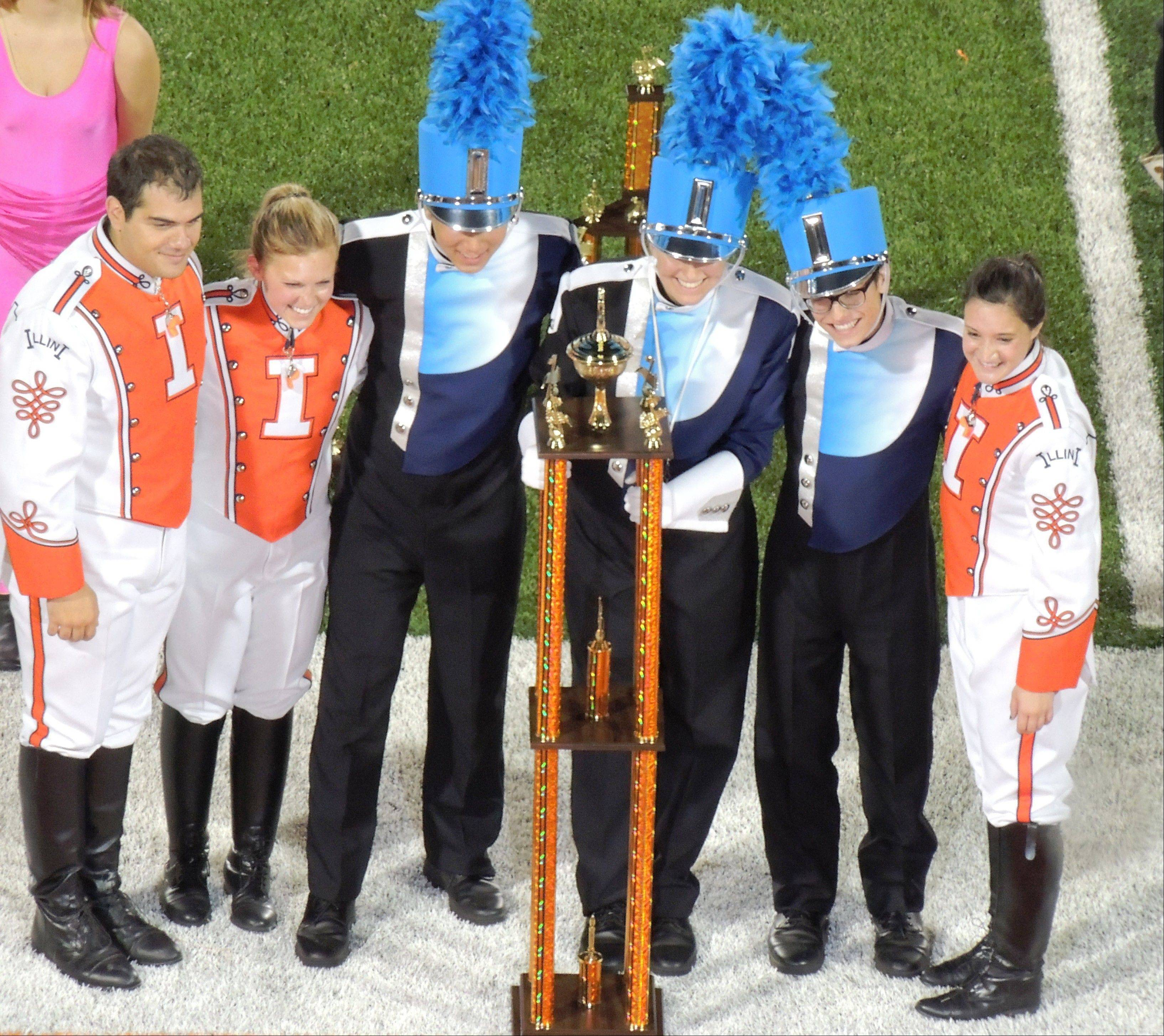 Prospect Marching Knights drum majors (in blue and white) Alex Yoo, left center, Destiny Duraj, center and Ted Marzolf, right center, accept the Grand Championship trophy.