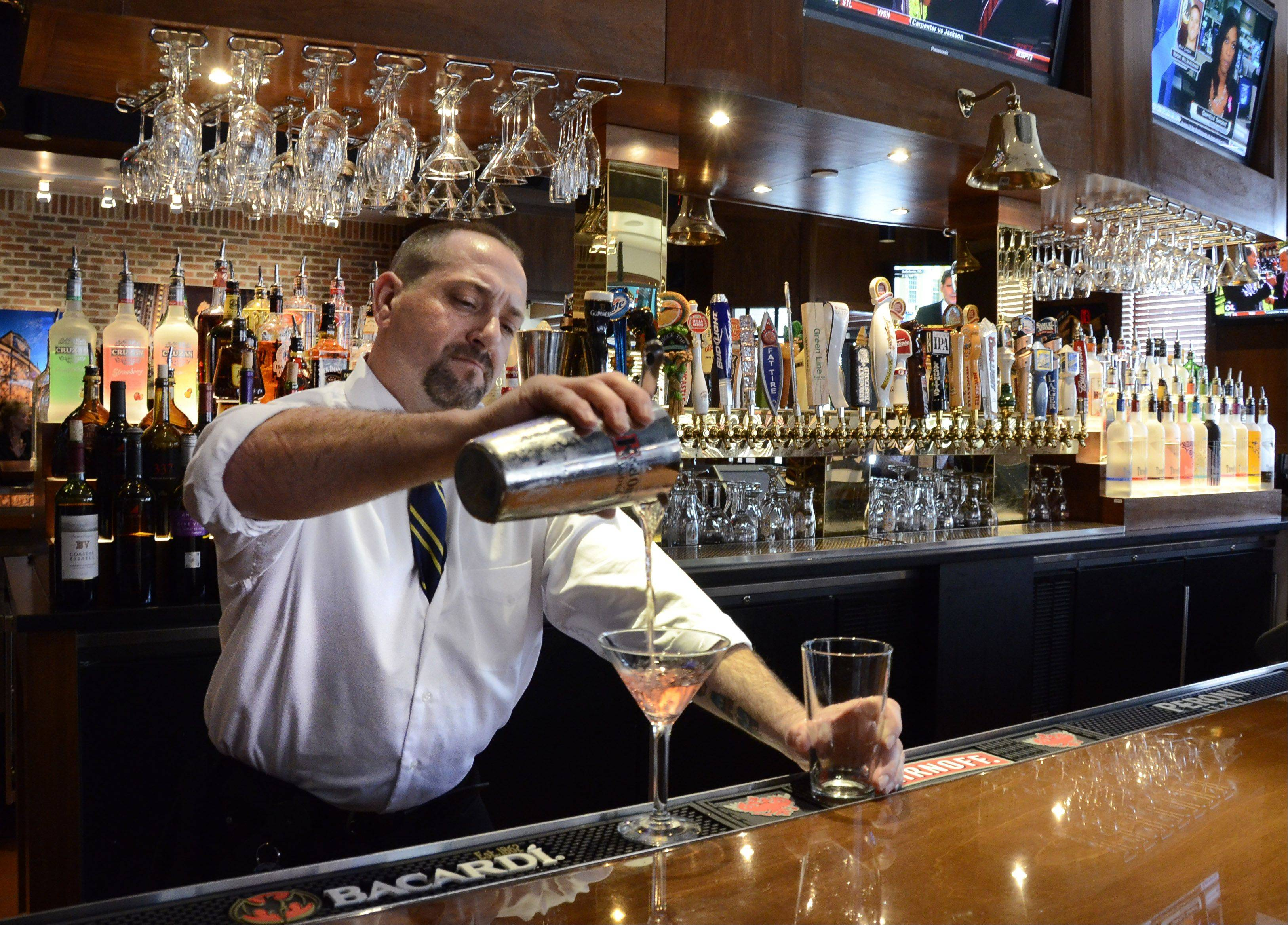 Bartender Niko Callas pours a cocktail at BlackFinn American Grill in Randhurst Village.