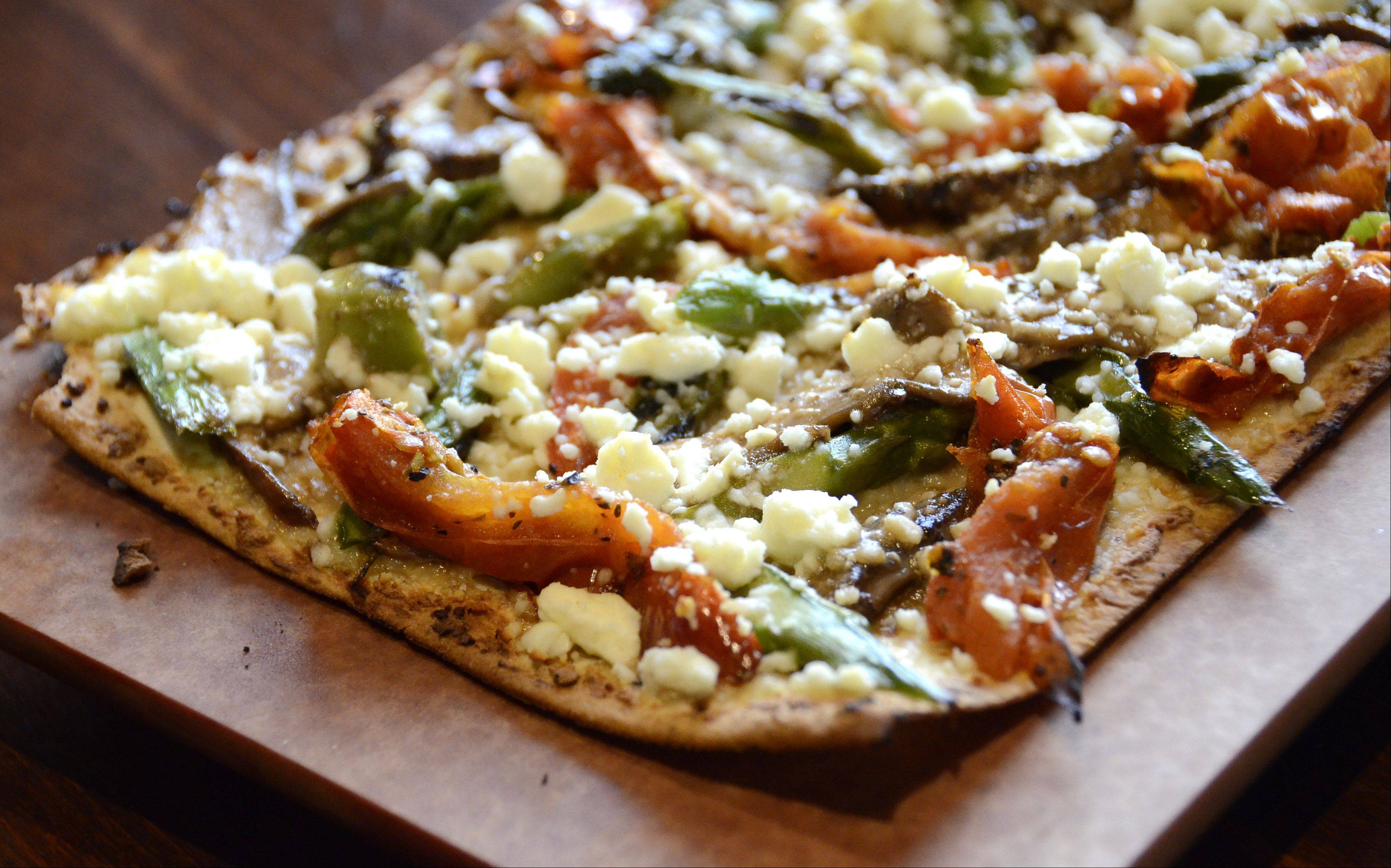 Roasted vegetable flatbread comes with roasted asparagus, tomatoes, garlic, balsamic portobello and feta cheese at BlackFinn American Grill in Mt. Prospect.