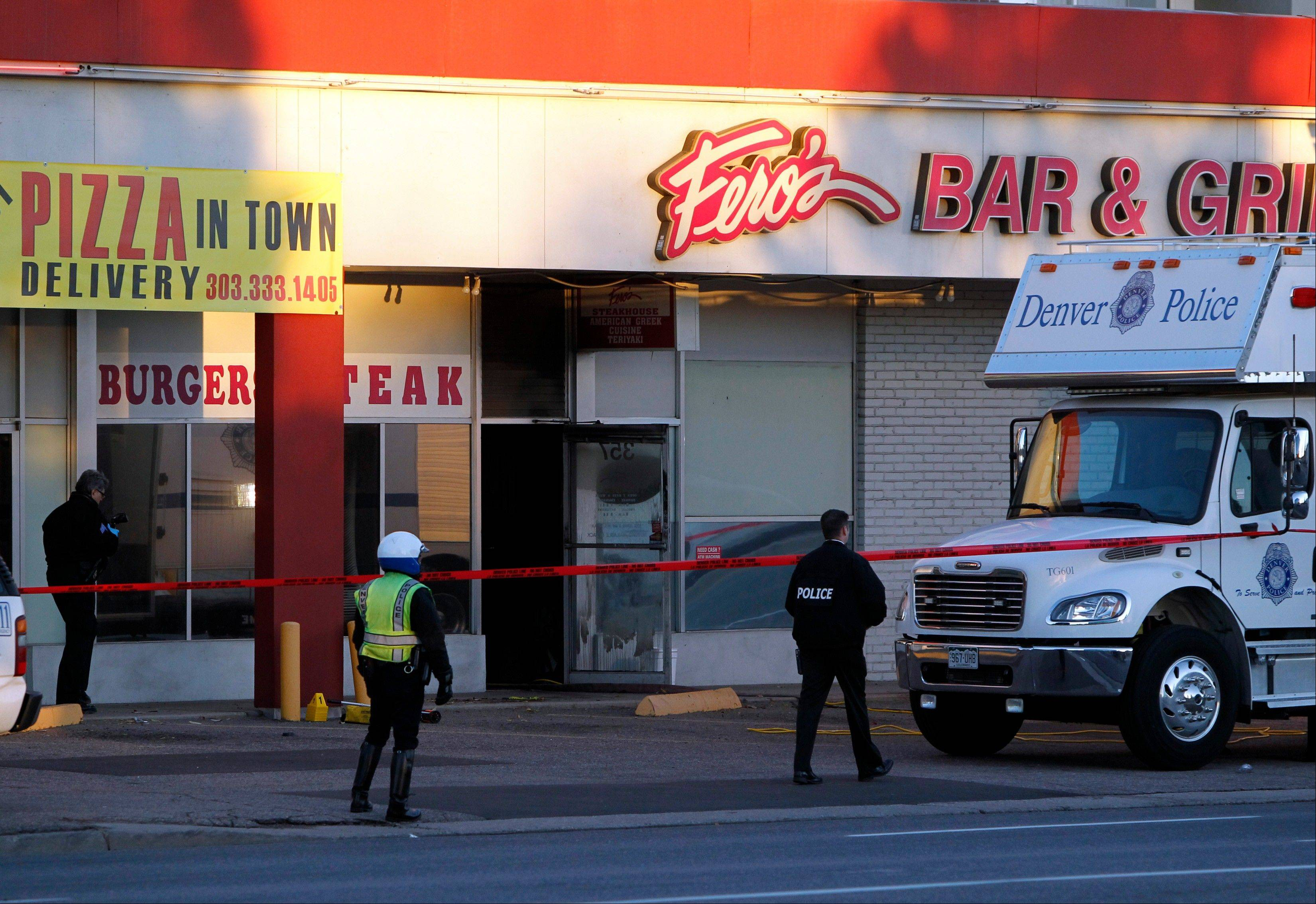 Police investigate at Fero's Bar and Grill in Denver on Wednesday, Oct. 17, 2012, where the bodies of a man and four woman were discovered after firefighters extinguished a fire at the bar early Wednesday morning. Police think the blaze was set to cover up their slayings.