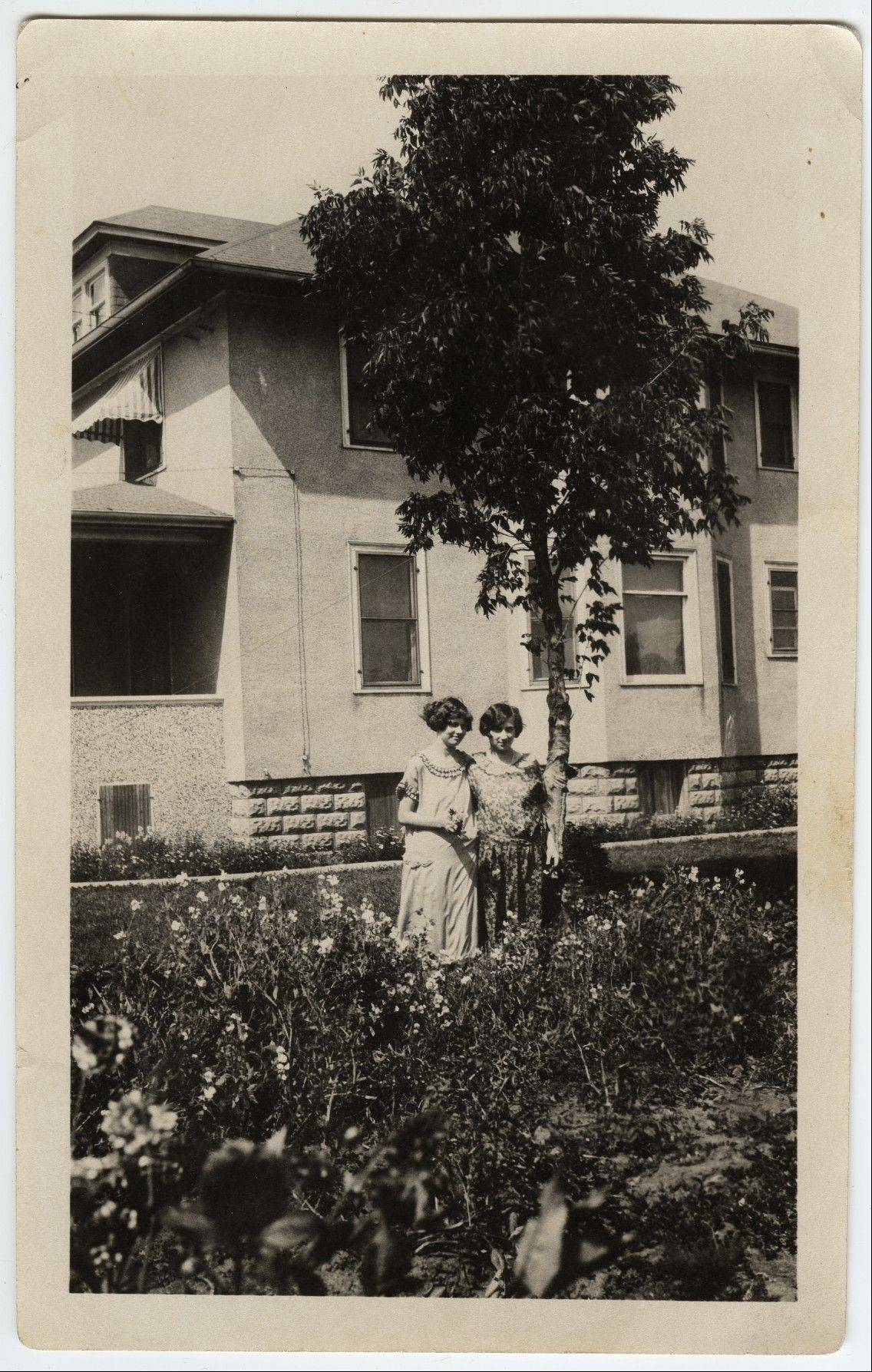 Magdalene Oltrogge Meyn and a friend stand near the Arlington Heights home that was originally stuccoed and later sided.