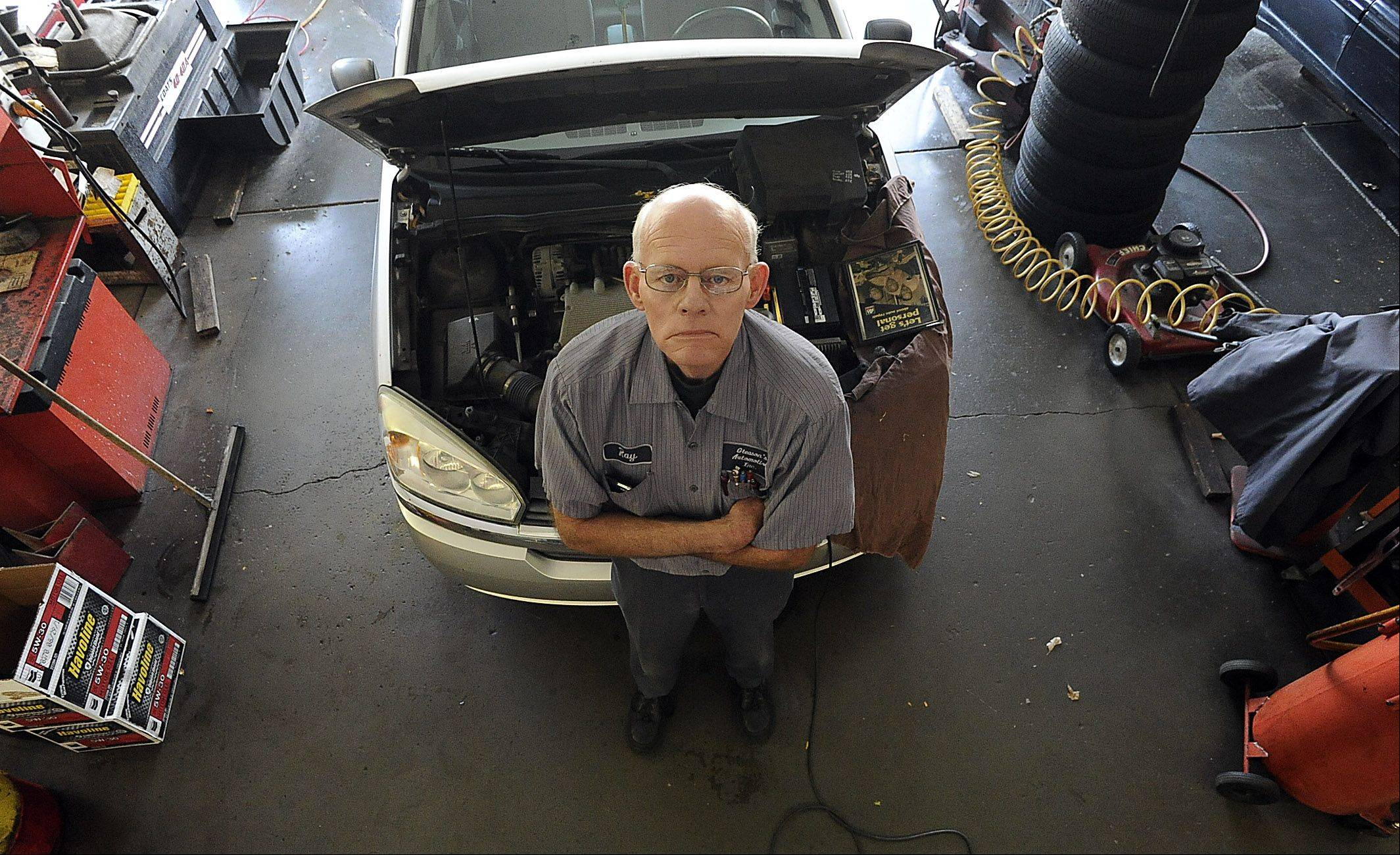 Ray Gleason stands inside his automotive shop in Des Plaines, where he is finishing up repair work on two cars. The business has been in the family 56 years.