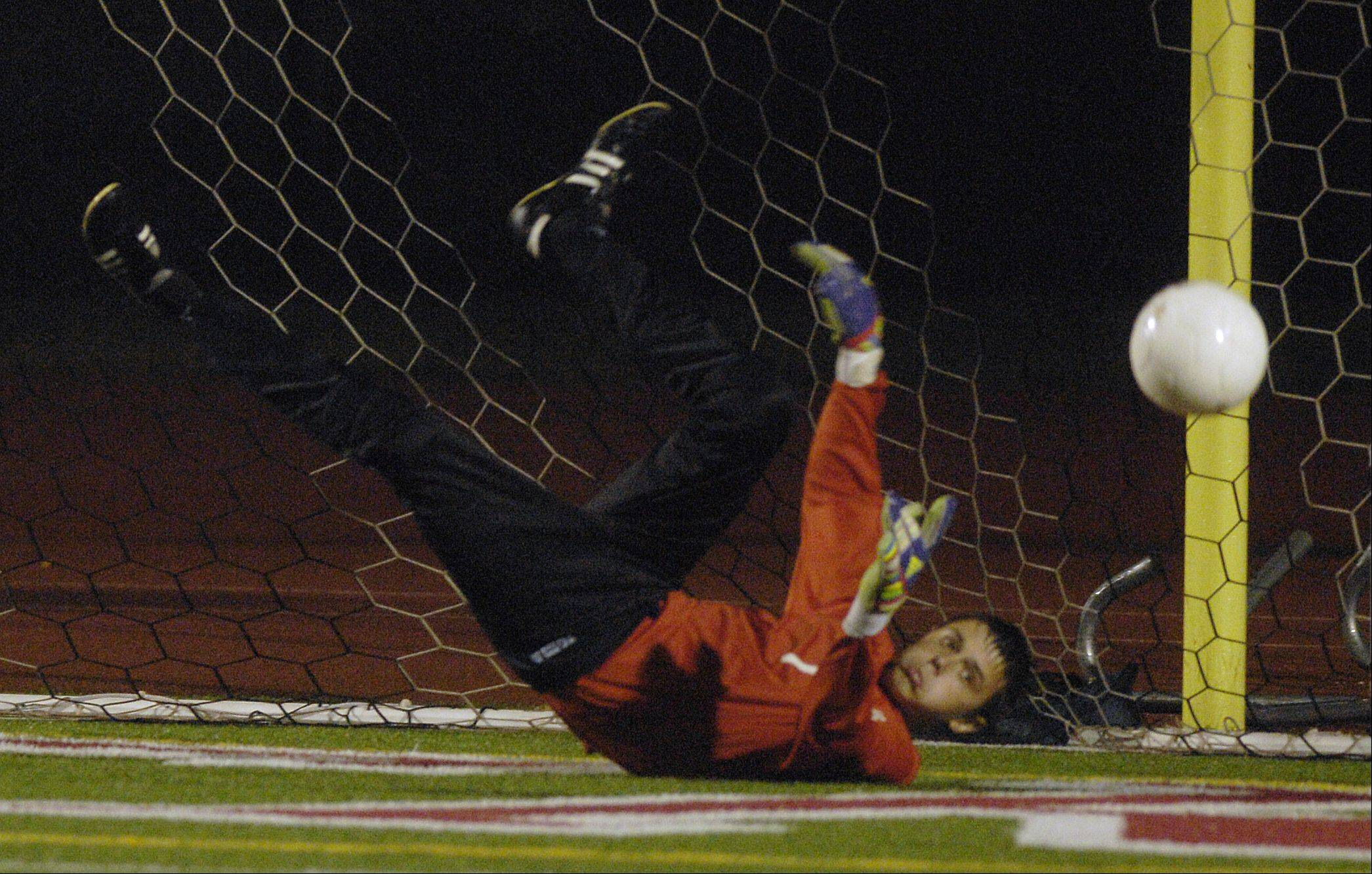 Goalkeeper Duncan Turnbull of Geneva blocks a shot on goal during his team's 7-0 loss to Naperville Central, in the boys soccer regional semifinals Wednesday in Naperville.