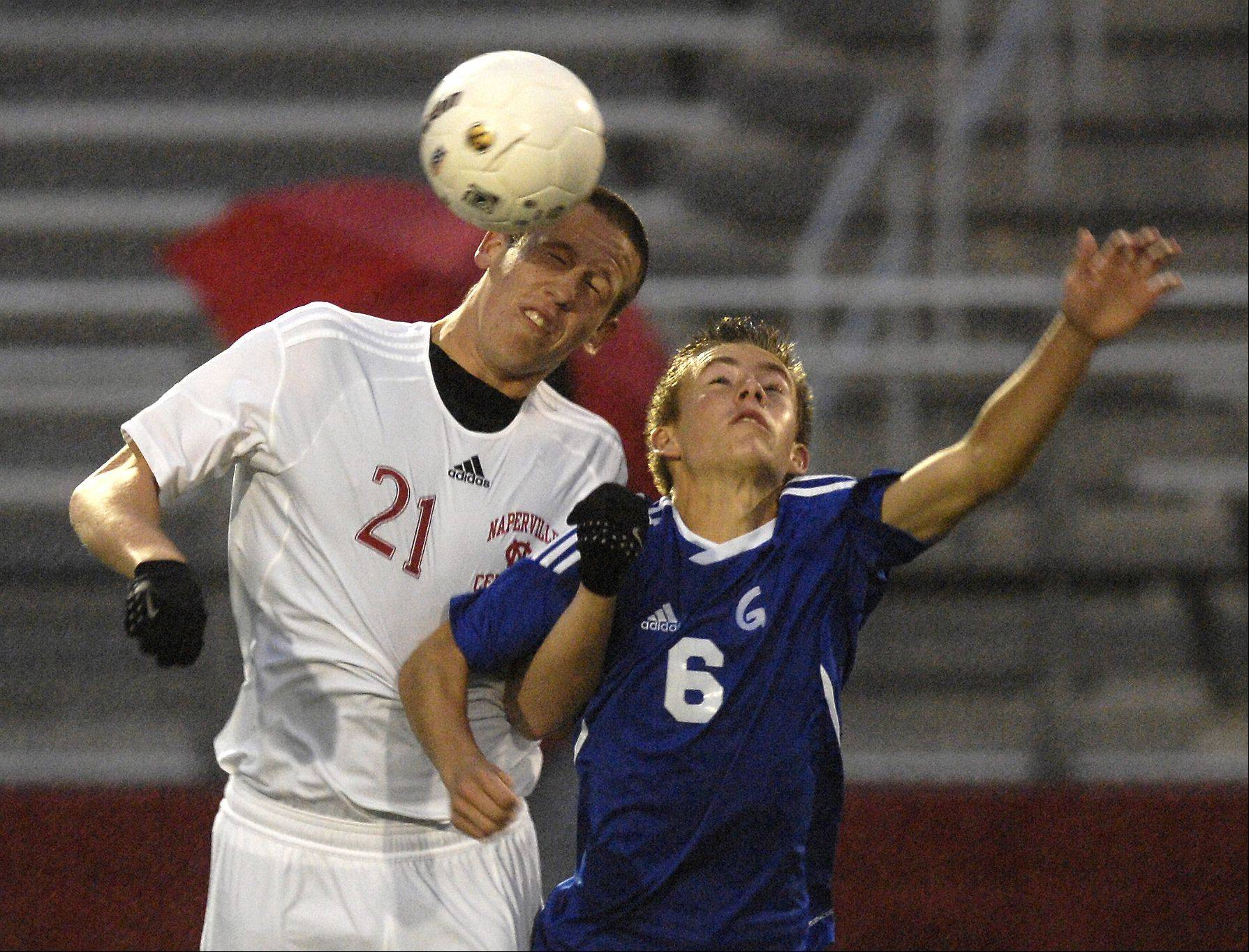 Jack Patrick of Naperville Central and Grant Bracken of Geneva battle for the ball during the Redhawks 7-0 win over the Vikings, in the boys soccer regional semifinals in Naperville, Wednesday.