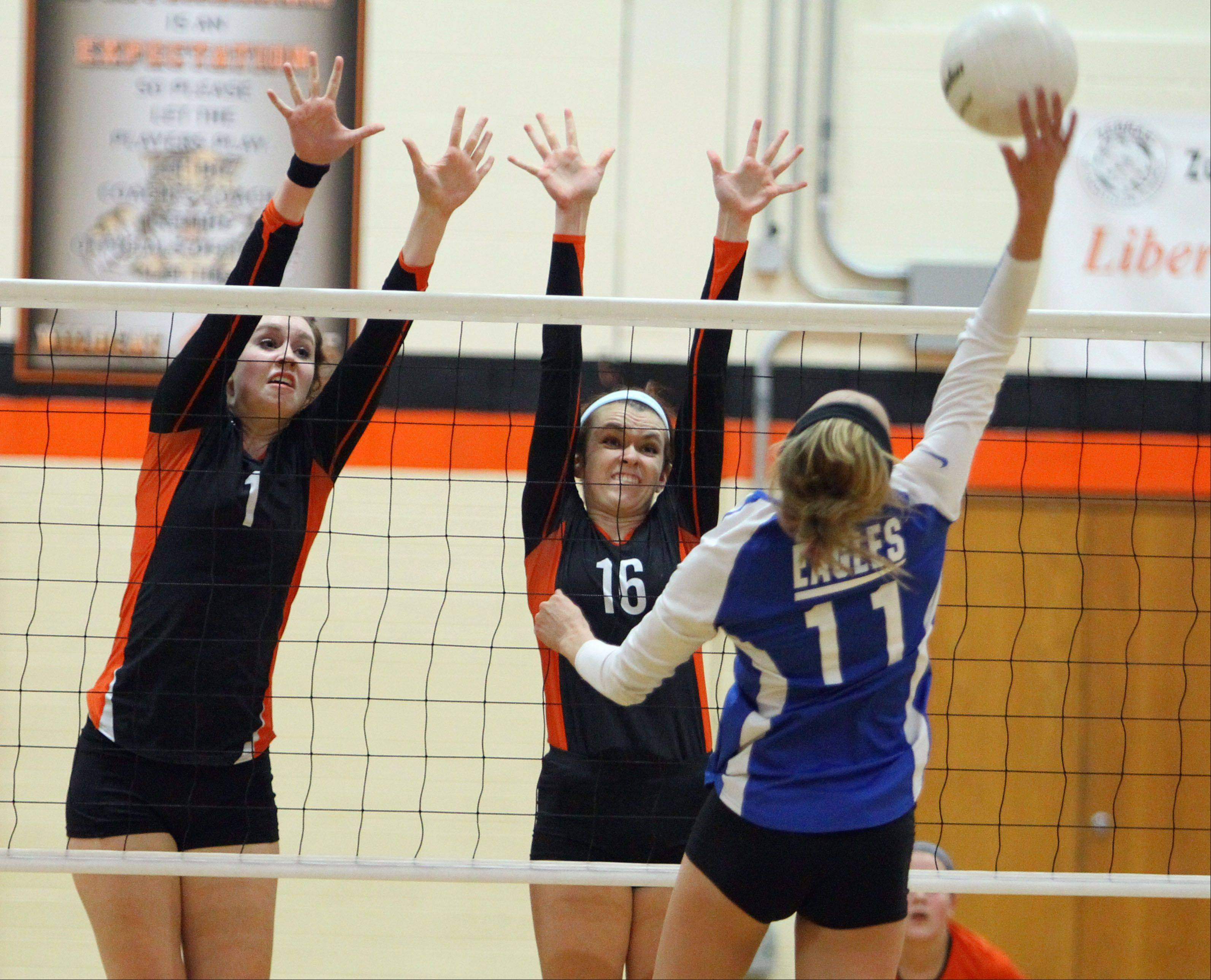 Lakes' Alex Silvola, right, spikes one at Libertyville's Alex Basler and Rhiannon Prentiss during the NSC title game Wednesday night at Libertyville.