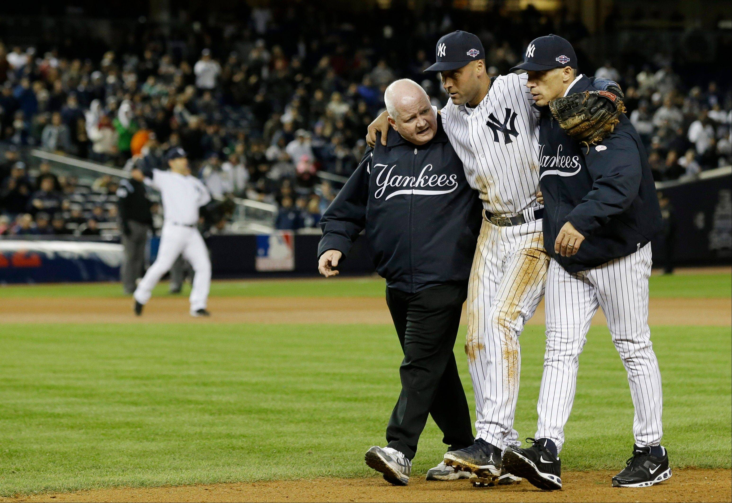 Trainer Steve Donohue, left, and New York Yankees manager Joe Girardi, right, help Derek Jeter off the field after he injured himself during Game 1 of the American League championship series against the Detroit Tigers Sunday, Oct. 14, 2012, in New York.