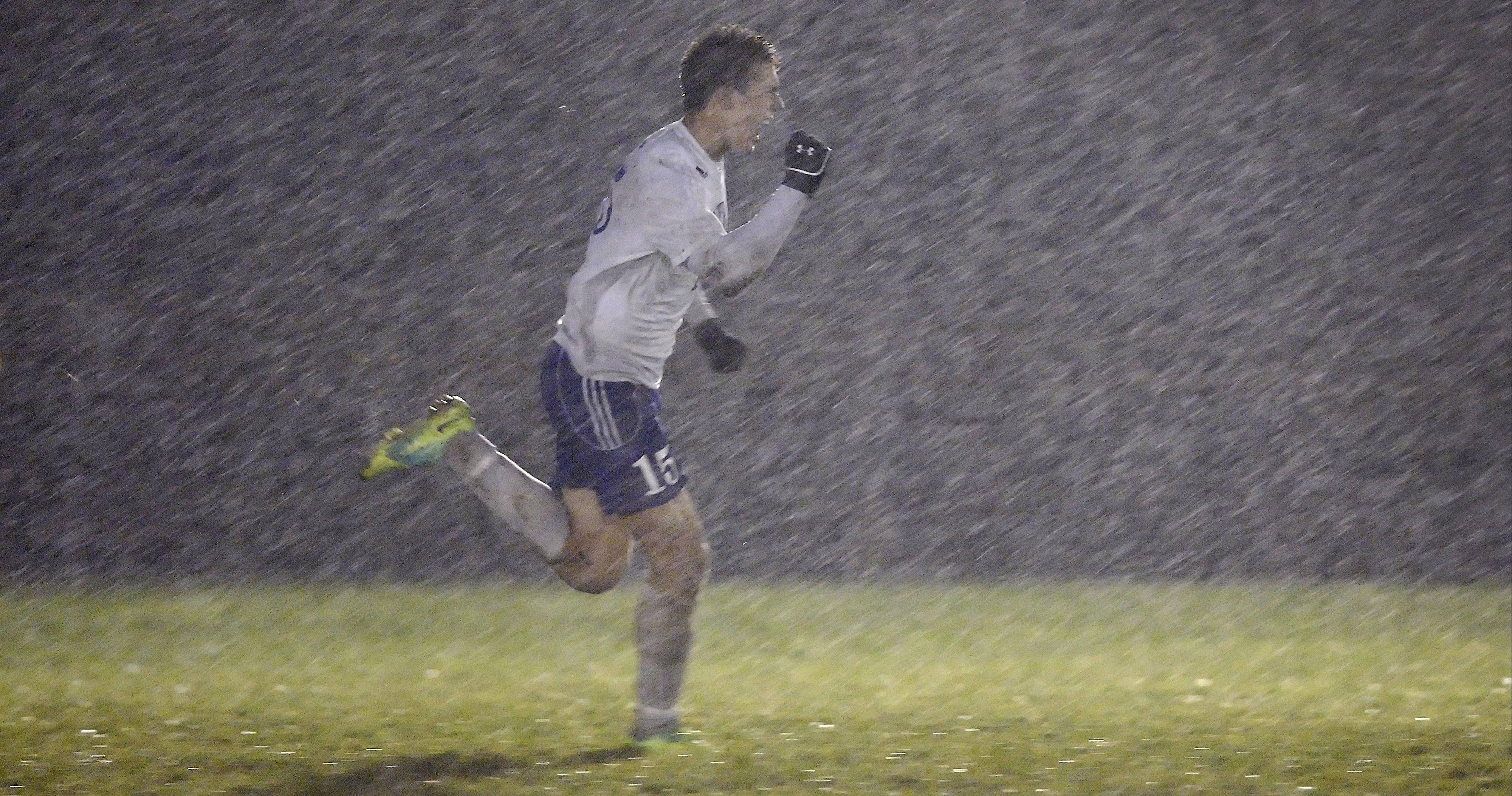 Burlington Central's Bryce Warner pumps his fist as he runs into the rain after scoring against Hampshire on a penalty kick in the first half Wednesday in the Burlington Central regional playoff game.