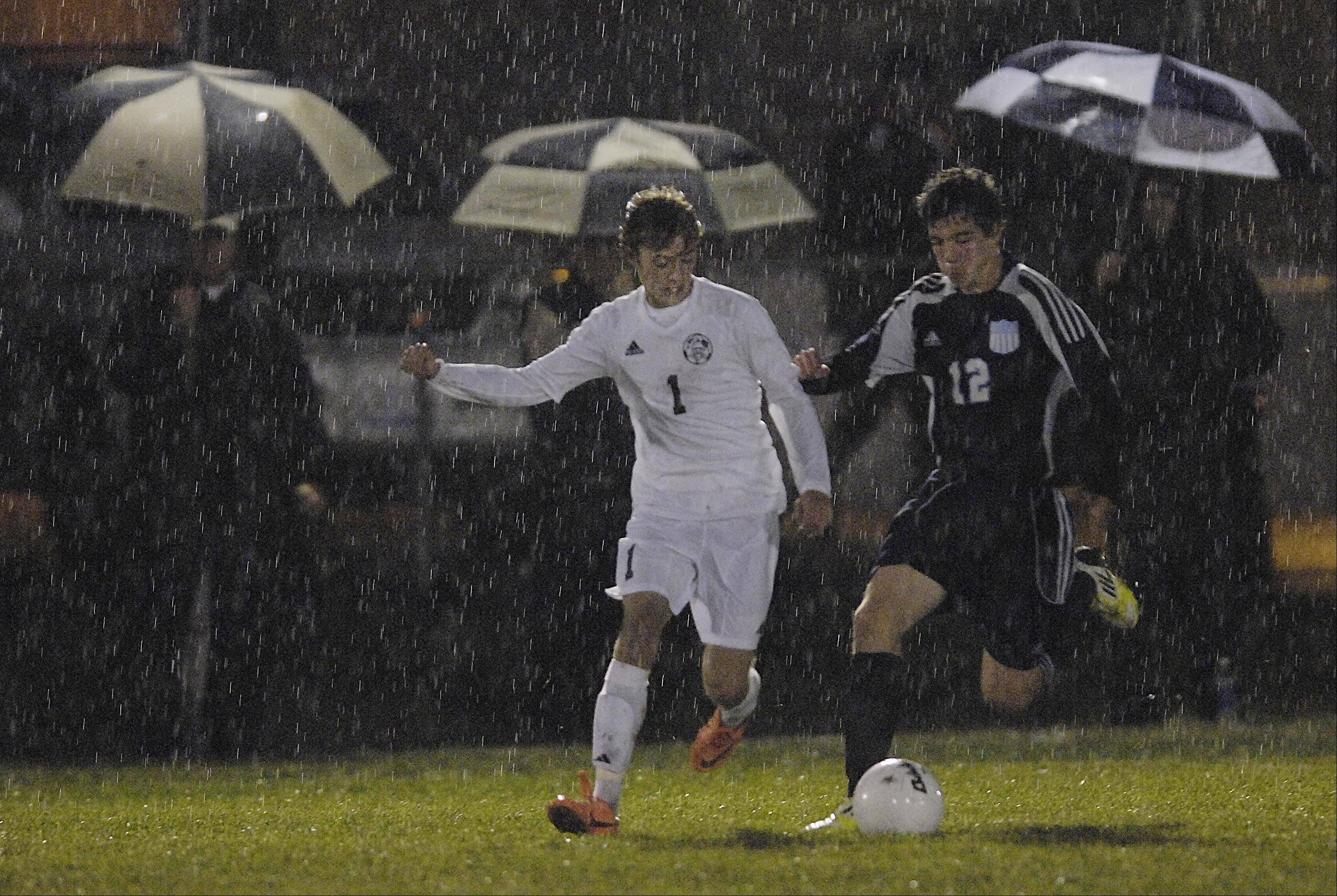 Kaneland's Tyler Siebert, left, and IMSA's Quinn Gungerevans chase the ball in the rain Wednesday in the Burlington regional playoff game.