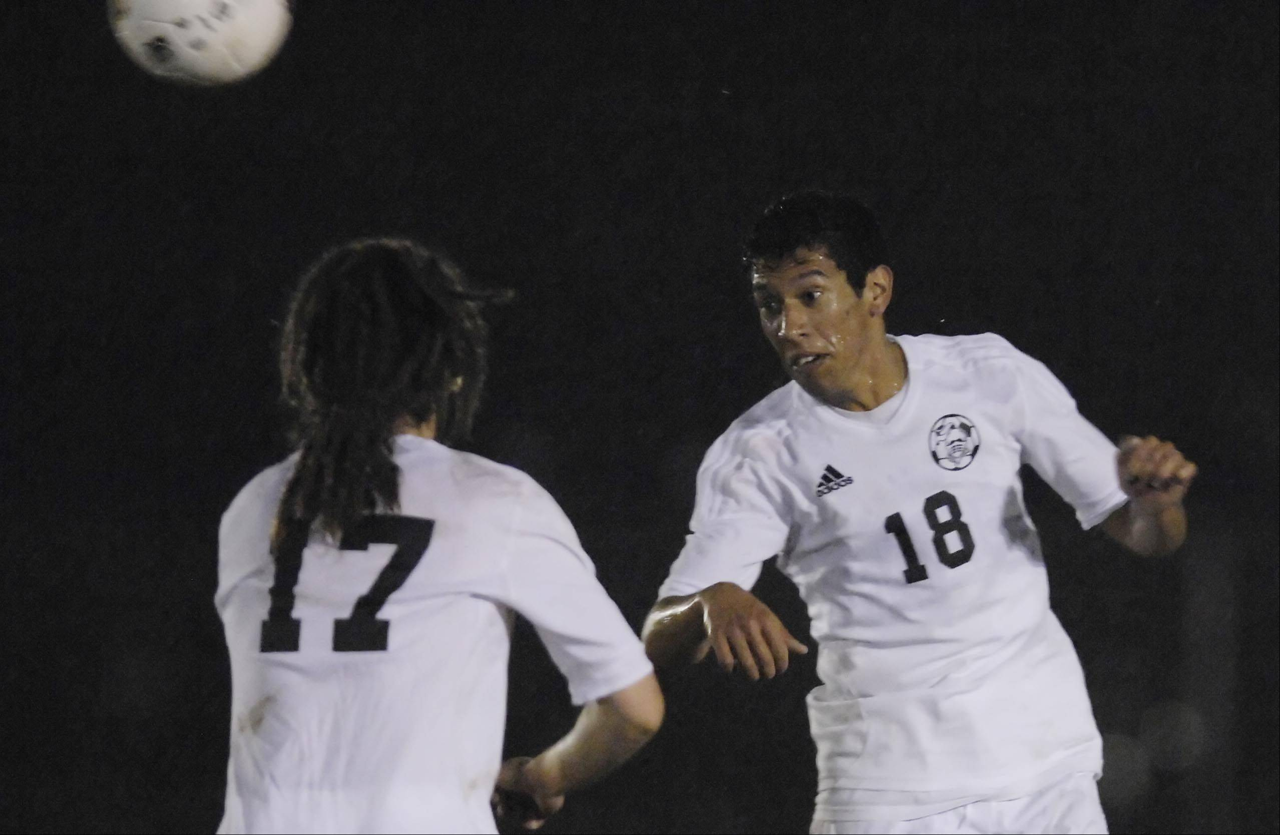 Kaneland's Diego Ochoa heads the ball as teammate Matt Vander Sande watches Wednesday in the Burlington regional playoff game against IMSA.
