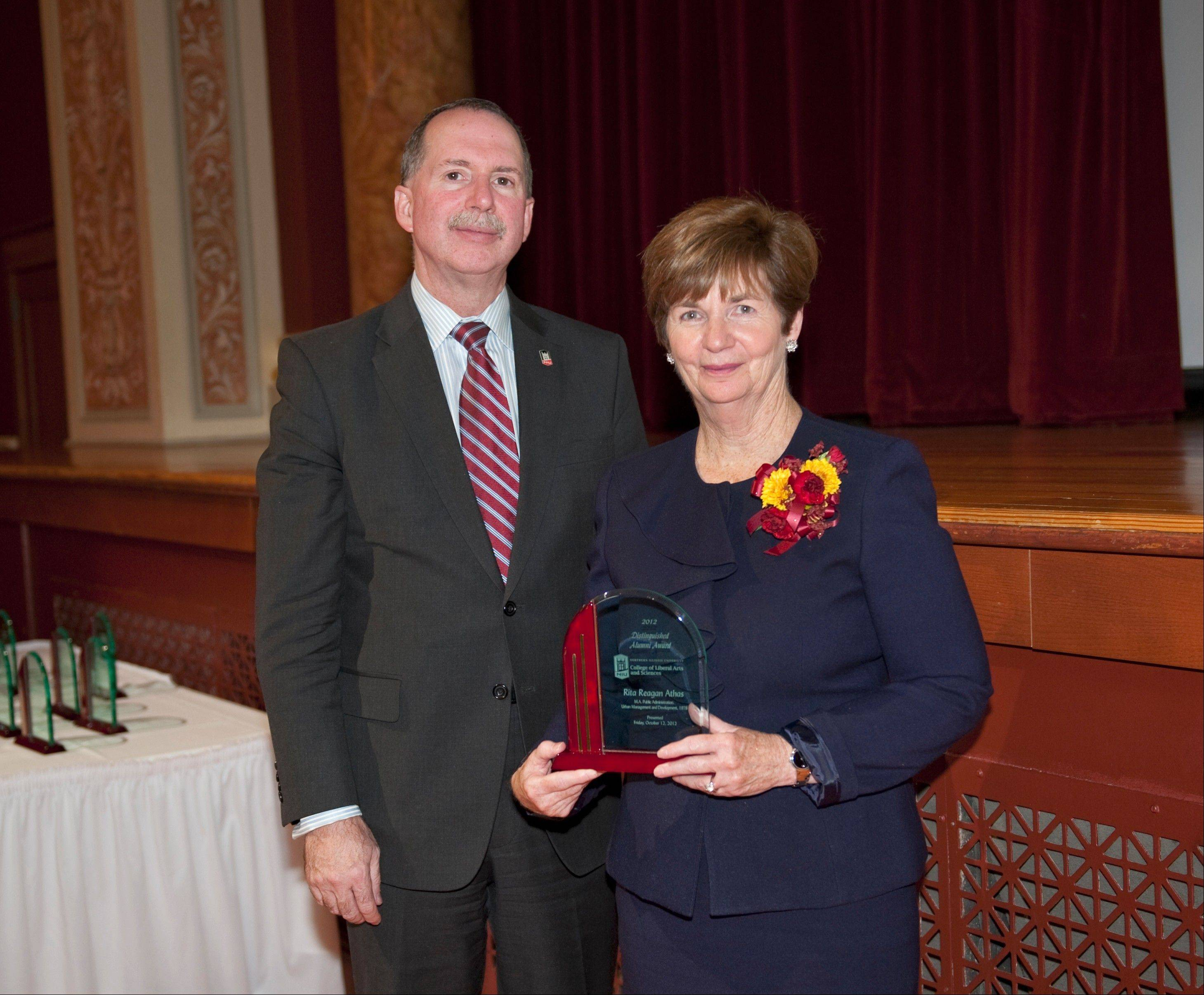 Rita Athas accepts a Distinguished Alumni Award from Christopher McCord.