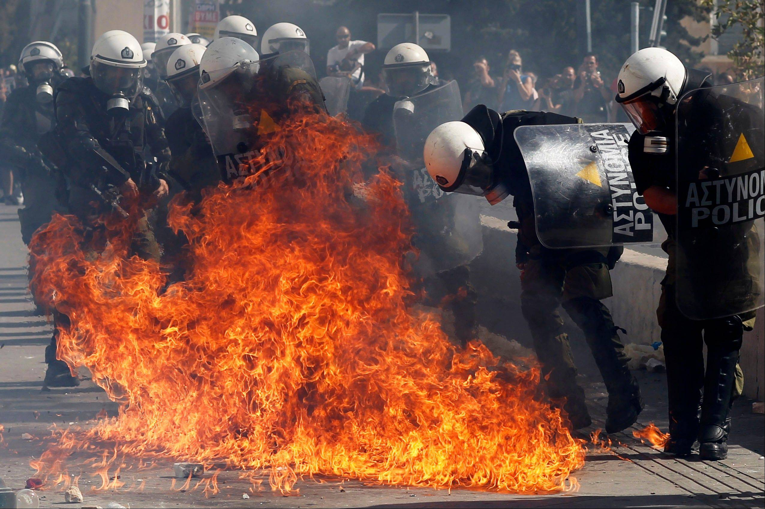 Associated Press Protesters throw petrol bombs at riot police officers during a 24-hour nationwide general strike in Athens on Thursday, Oct. 18, 2012. Hundreds of youths pelted riot police with petrol bombs, bottles and chunks of marble Thursday as yet another Greek anti-austerity demonstration descended into violence.