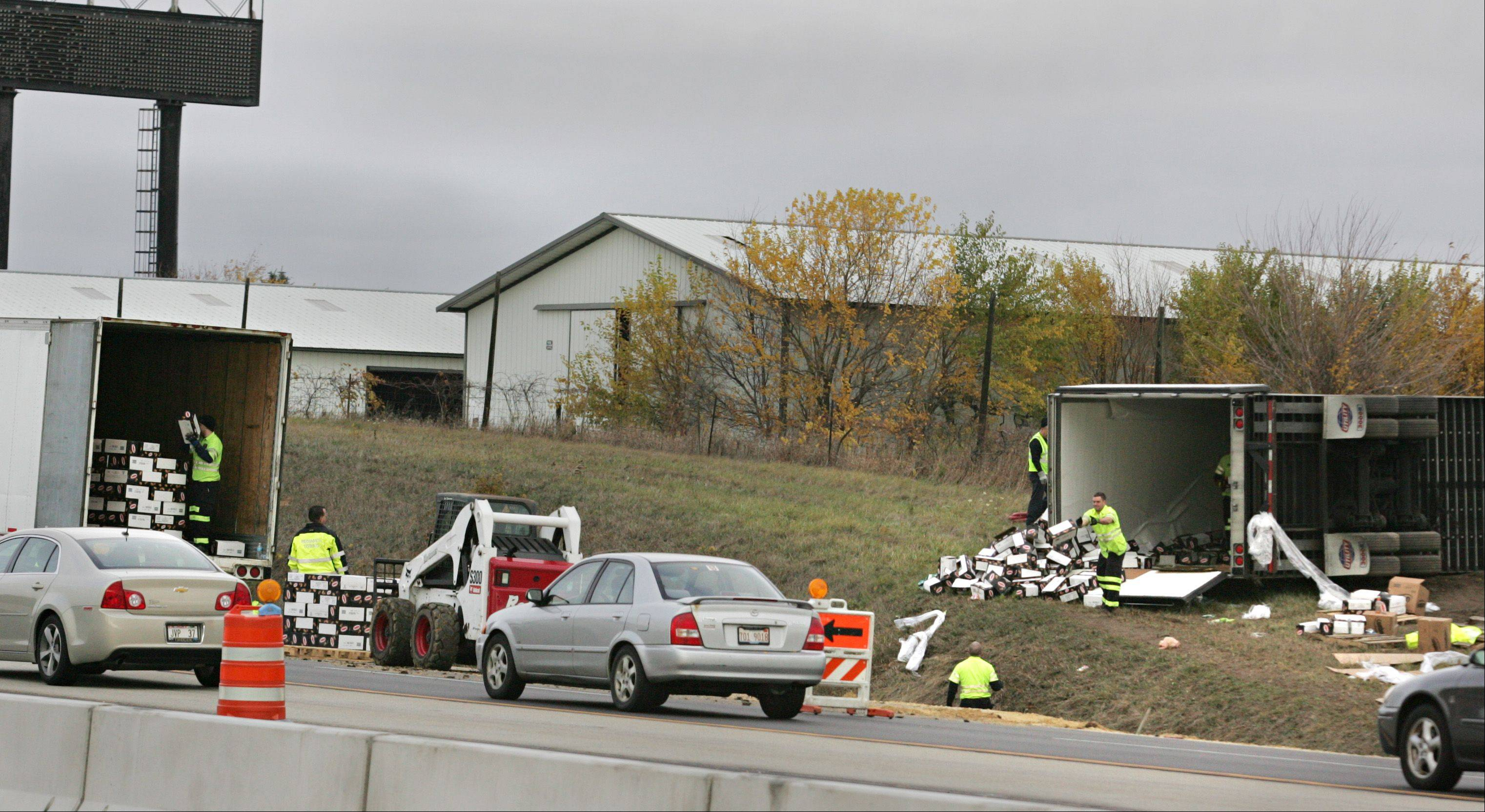 IDOT emergency crews unload boxes from a tractor trailer that crashed near the westbound lanes of the Jane Addams Tollway Thursday morning near Hampshire. The truck ended up well off the north side of the roadway, roughly one half mile before the exit to Route 20.