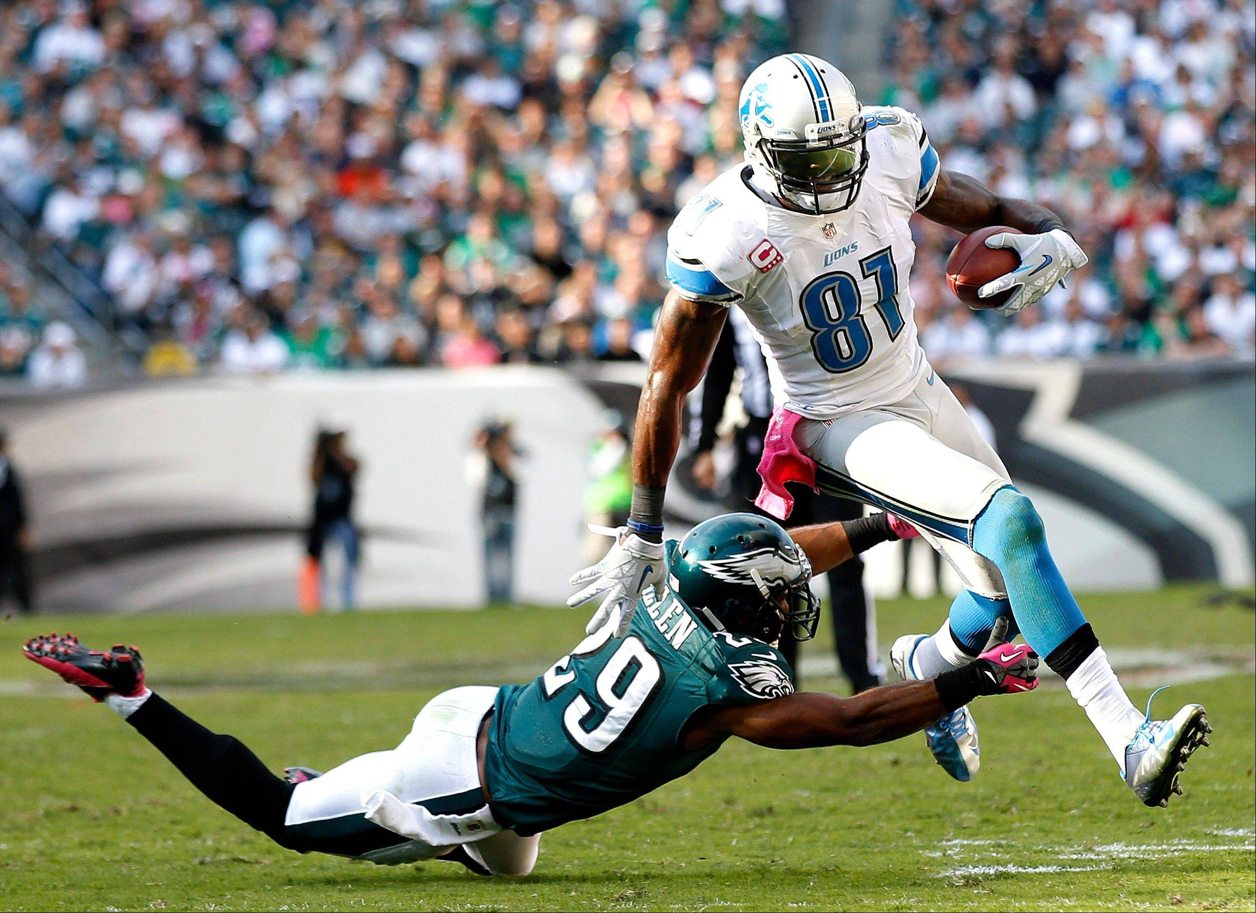Lions wide receiver Calvin Johnson (81) avoids a tackle by Philadelphia Eagles strong safety Nate Allen (29) during the second half an NFL football game, Sunday, Oct. 14, 2012, in Philadelphia. (AP Photo/Mel Evans)