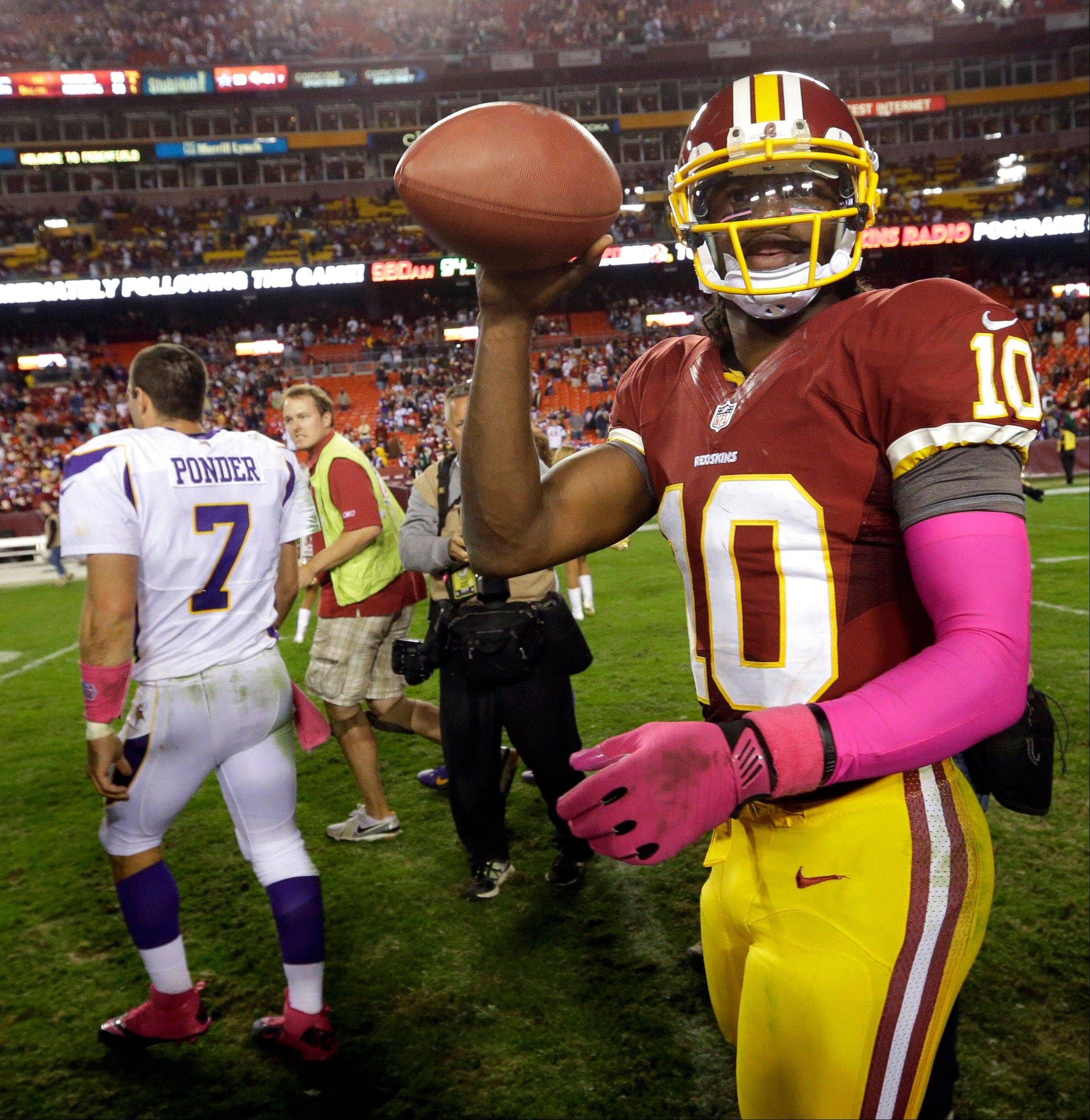 Washington Redskins quarterback Robert Griffin III tosses a game ball to a team employee Sunday after the Redskins beat the Minnesota Vikings 38-26.