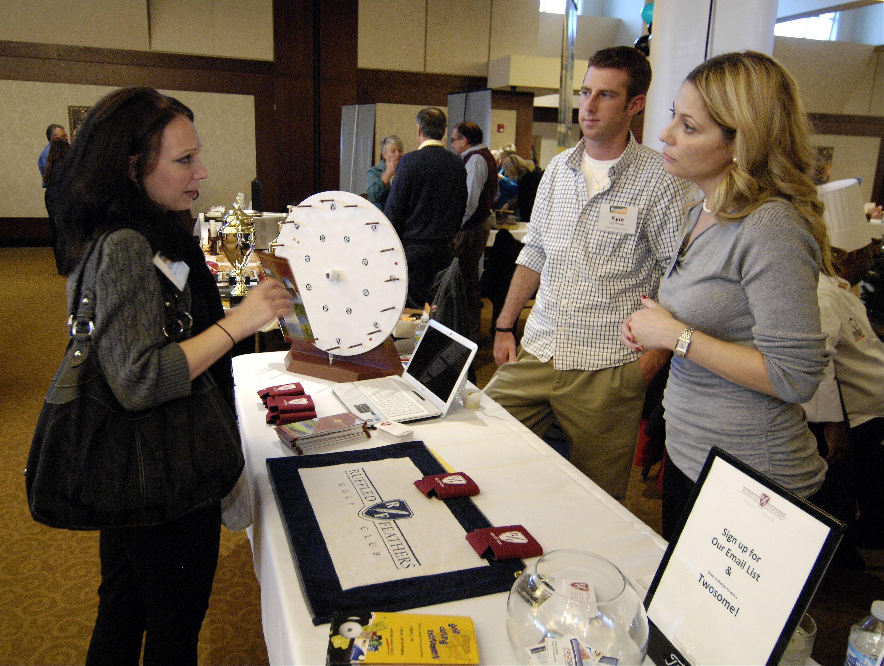 DAILY HERALD/Mark BlackAlison Glickman of Fast Signs in Oakbrook Terrace talks with Kyle Goergen and Lisa Lutz of Ruffled Feathers golf course in Lemont during the Daily Herald Business Ledger Hospitality Expo in Woodridge, Thursday.