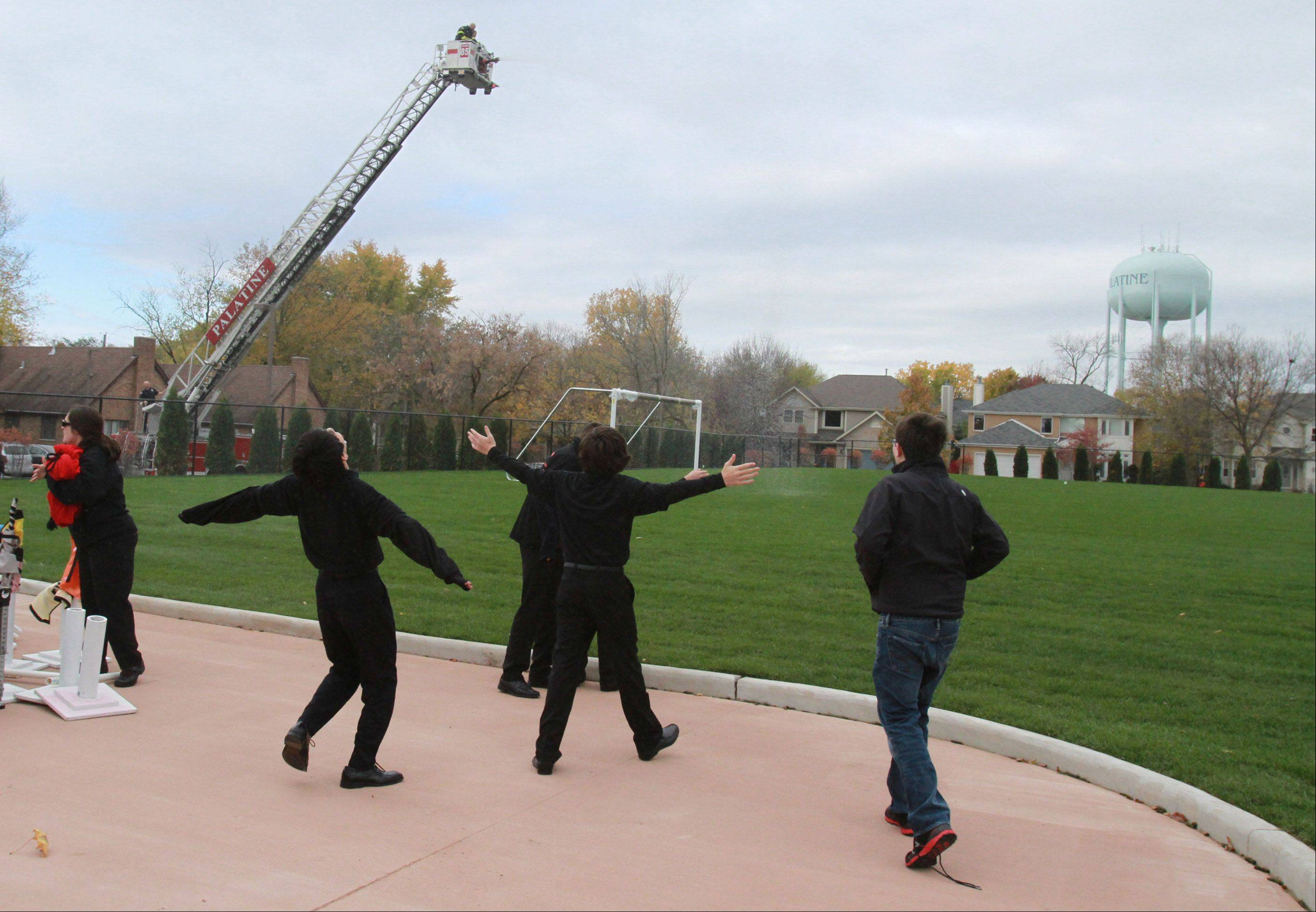 Quest Academy students welcome a wall of water on the athletic fields as the Palatine Fire Department christens the school's new 3.68-acre outdoor West Campus Thursday.