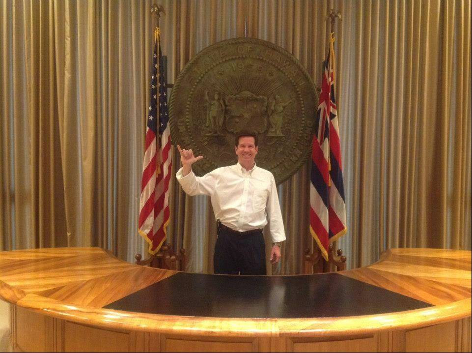 "Flashing the shaka sign commonly used to express a ""hang loose"" aloha culture, Mickey Straub has fun in the office of the Hawaiian governor."
