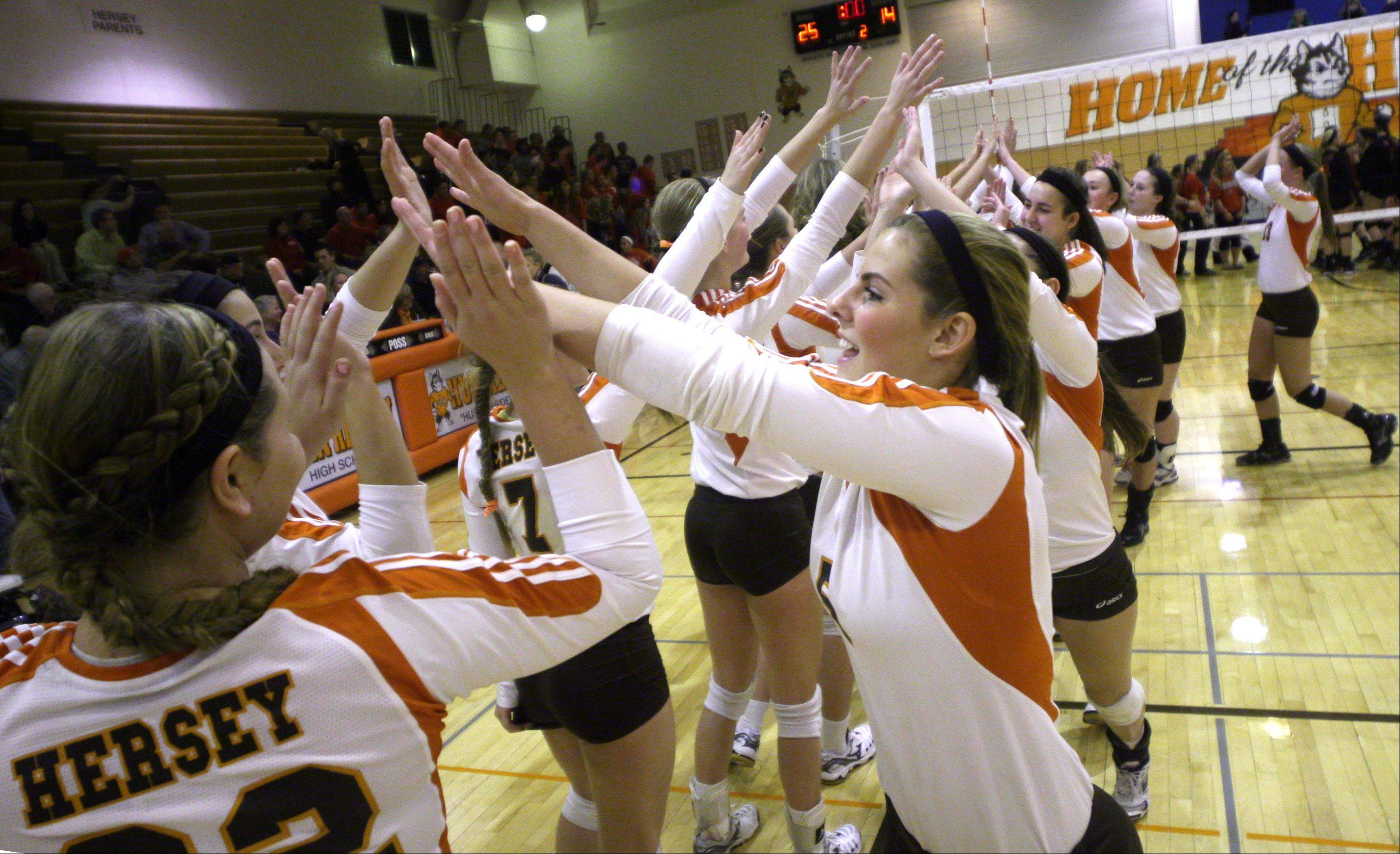 The Hersey Huskies, including Michelle Brown, center, begin a celebration after knocking off Palatine in the Mid-Suburban League championship volleyball game in Arlington Heights on Thursday night.