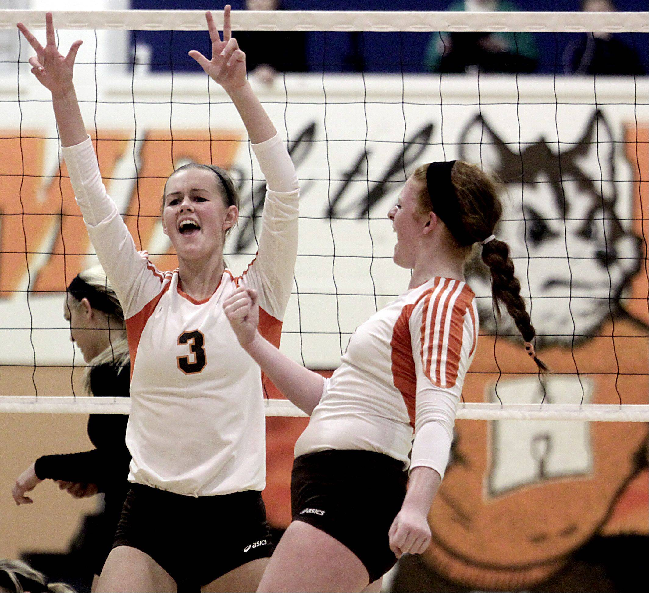 Hersey's Erica Hill, left, and Abby Fesl celebrate a point against Palatine during the Mid-Suburban League championship volleyball game in Arlington Heights on Thursday night.