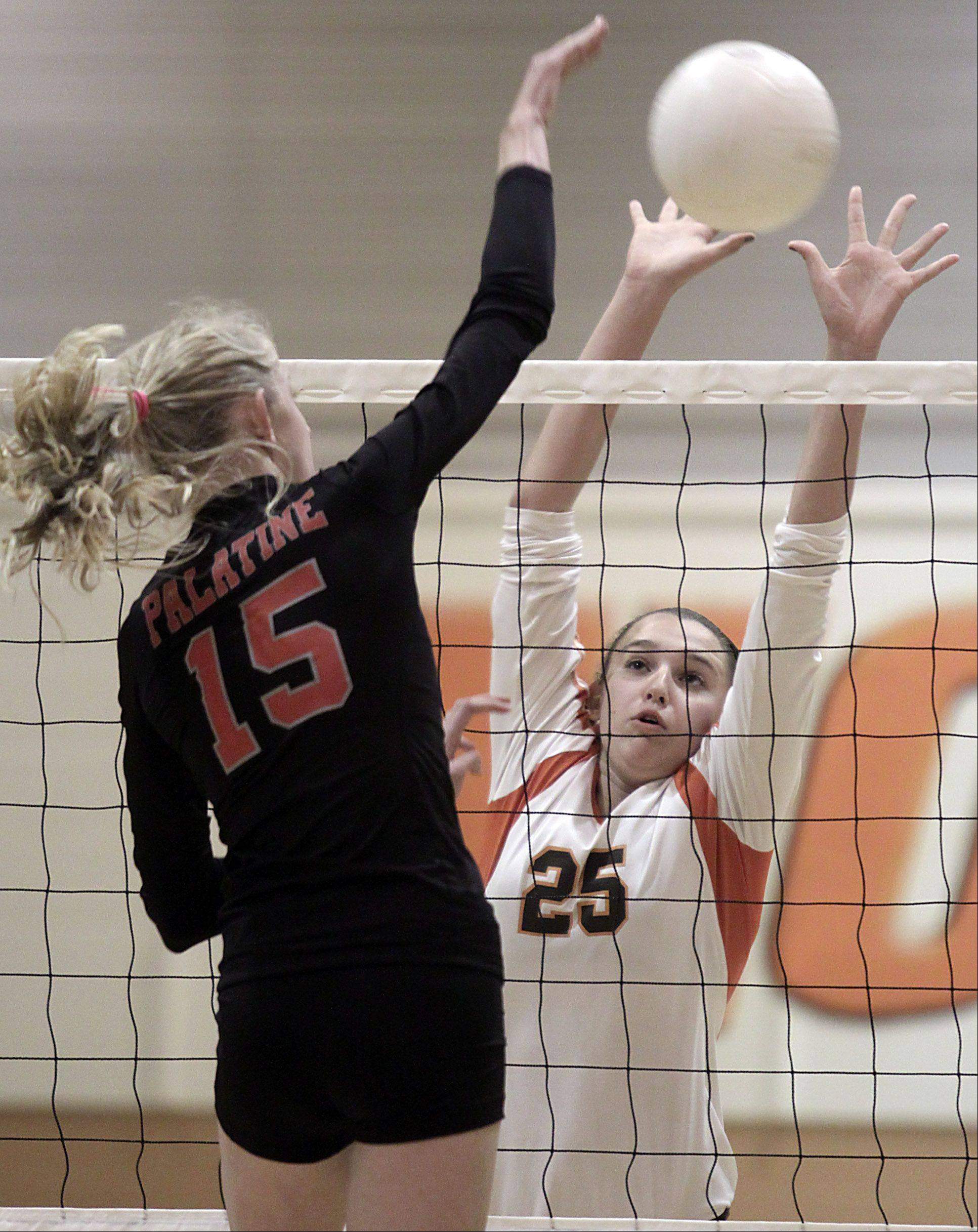 Hersey's Gabriella Olhava, right, blocks Palatine's Kim Butler during the Mid-Suburban League championship volleyball game in Arlington Heights on Thursday night.