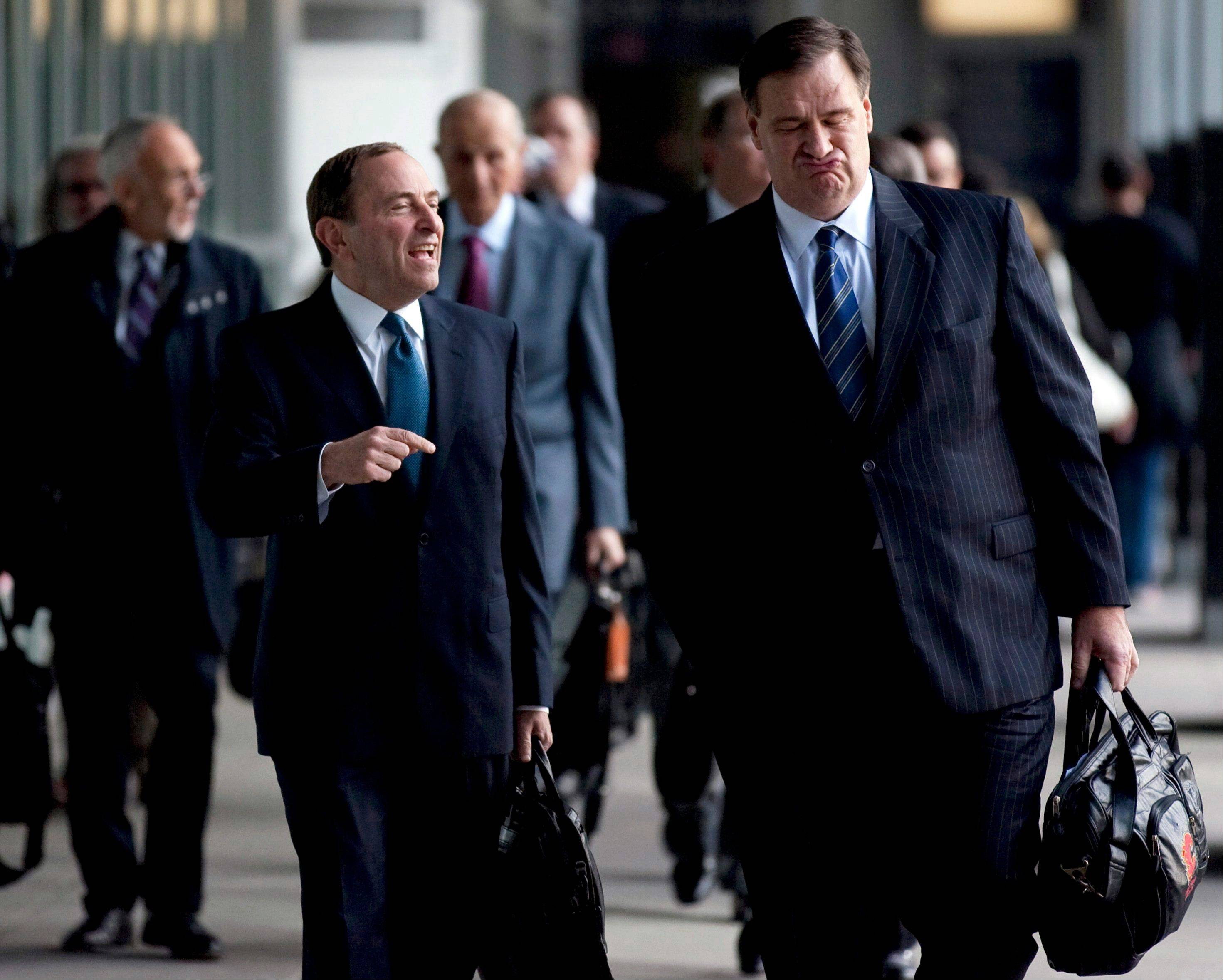 NHL Commissioner Gary Bettman, left foreground, and Calgary Flames co-owner Murray Edwards arrive for negotiations with the NHL Players Association in Toronto Thursday.