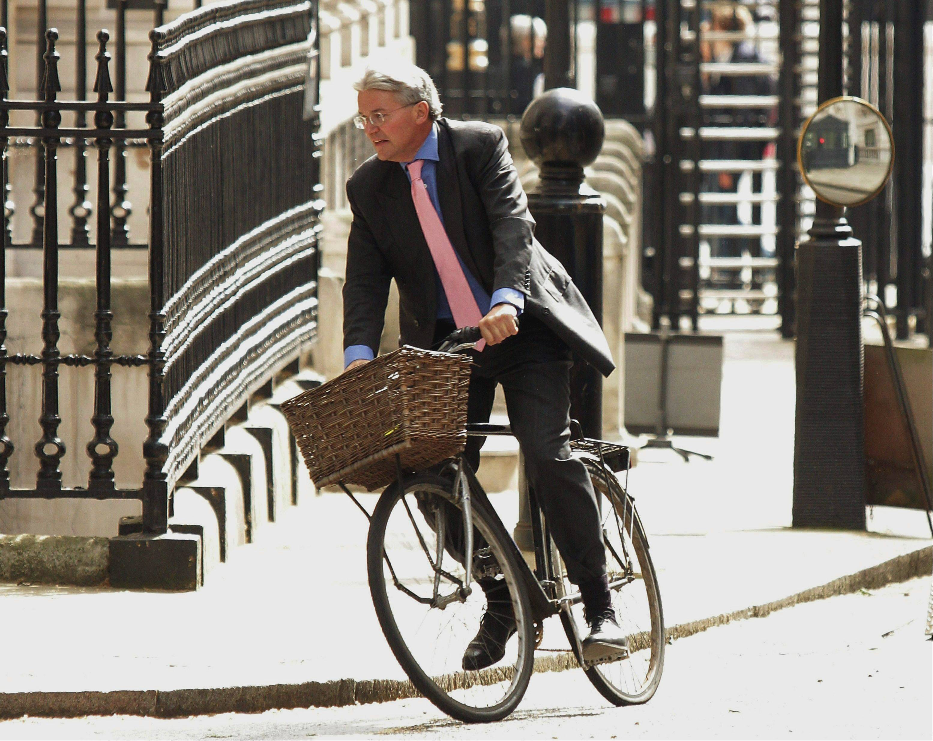 Government chief whip Andrew Mitchell arrives at Downing Street, London, on his bike.